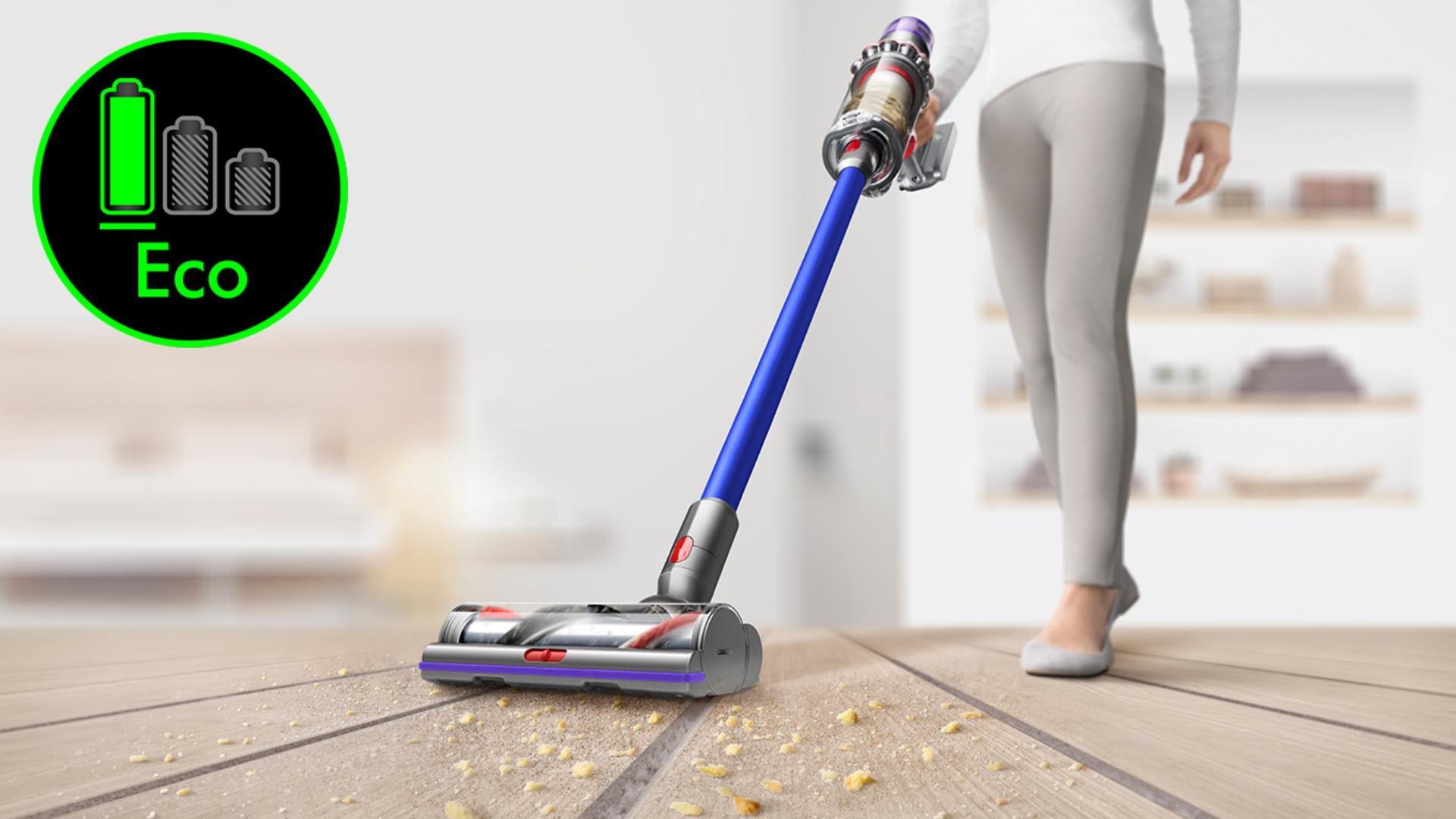 Dyson V11 vacuum cleaner picking up debris from hard floor in the corner is the eco mode logo.