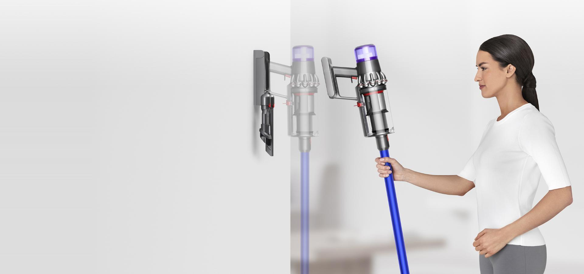 Woman placing Dyson V11™ vacuum into wall charging dock