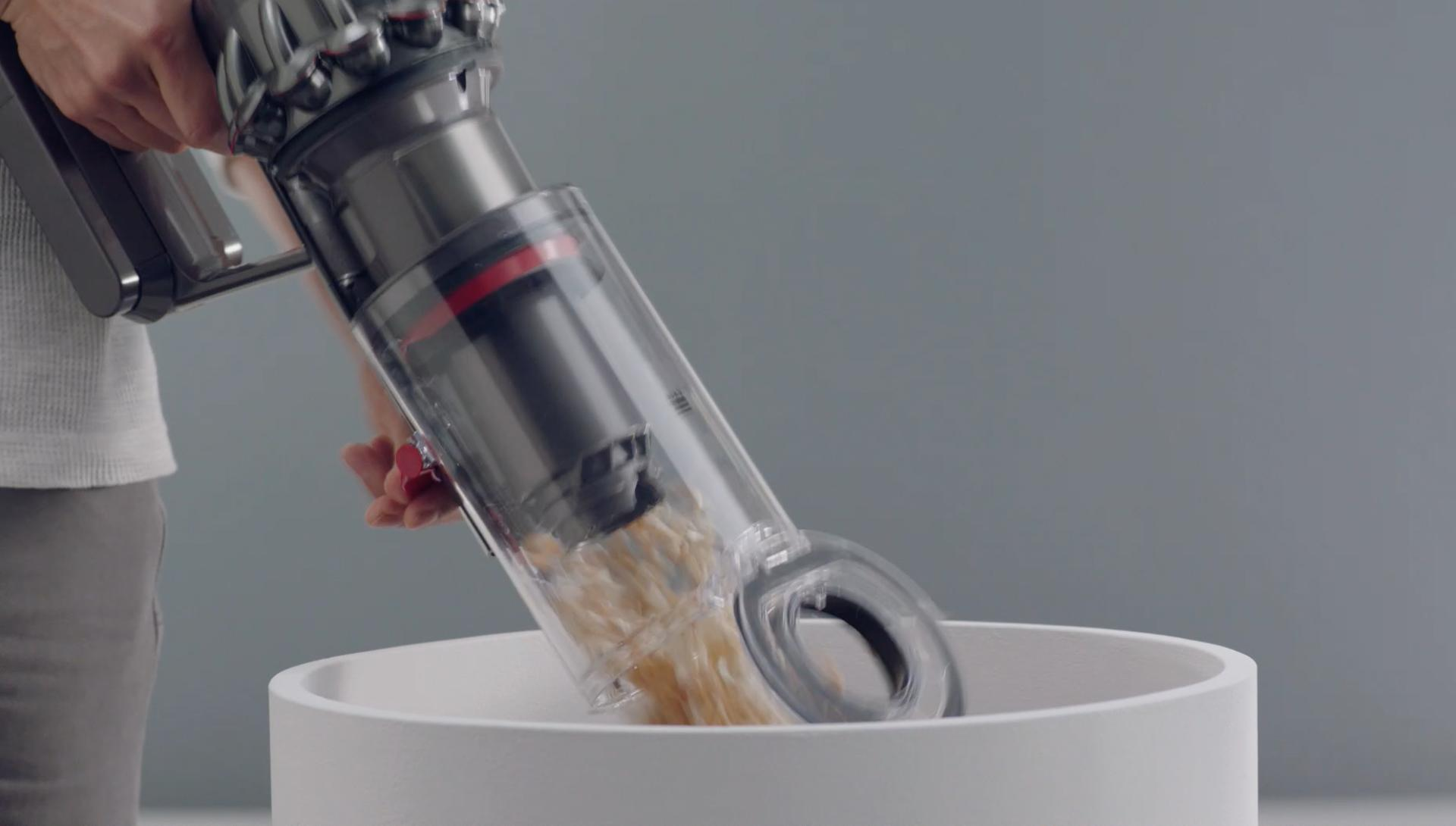 Dyson V11 vacuum cleaner being emptied into a bin