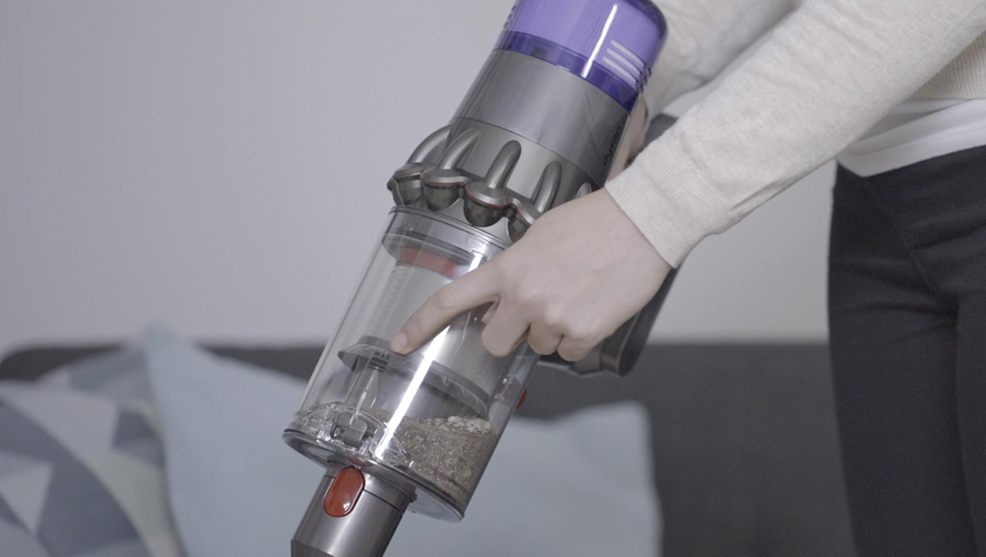 Woman pointing to the MAX marker on the Dyson V11™ bin