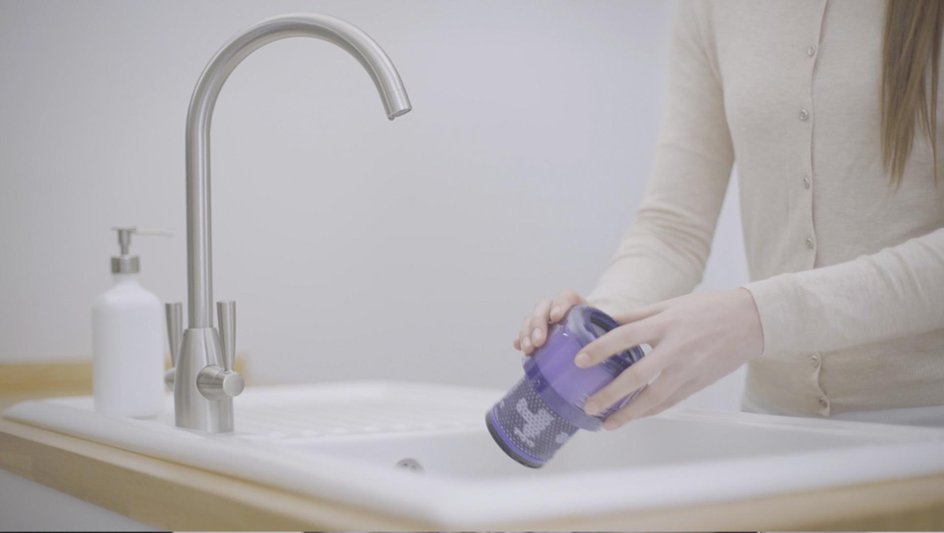 Woman washing the Dyson V11™ vacuum filter