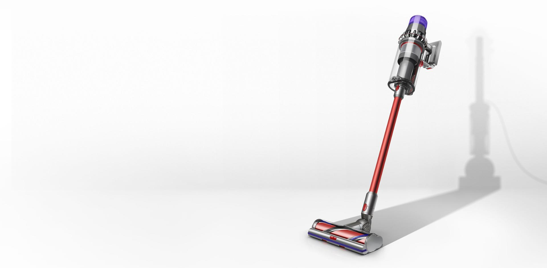 A Dyson V11 Outsize cordless vacuum with the shadow of a corded cleaner