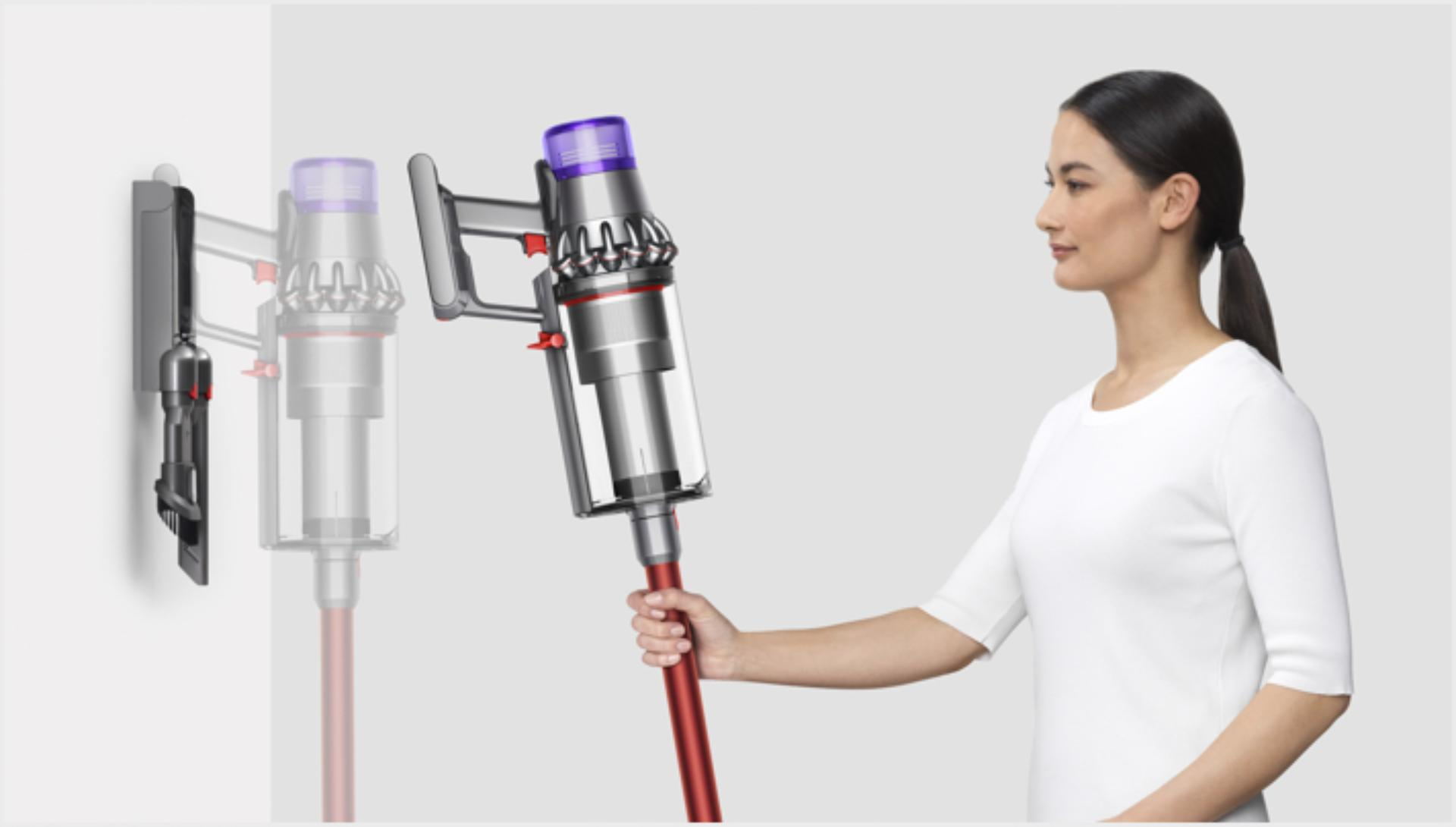 Woman placing Dyson V11 Outsize vacuum into wall charging dock