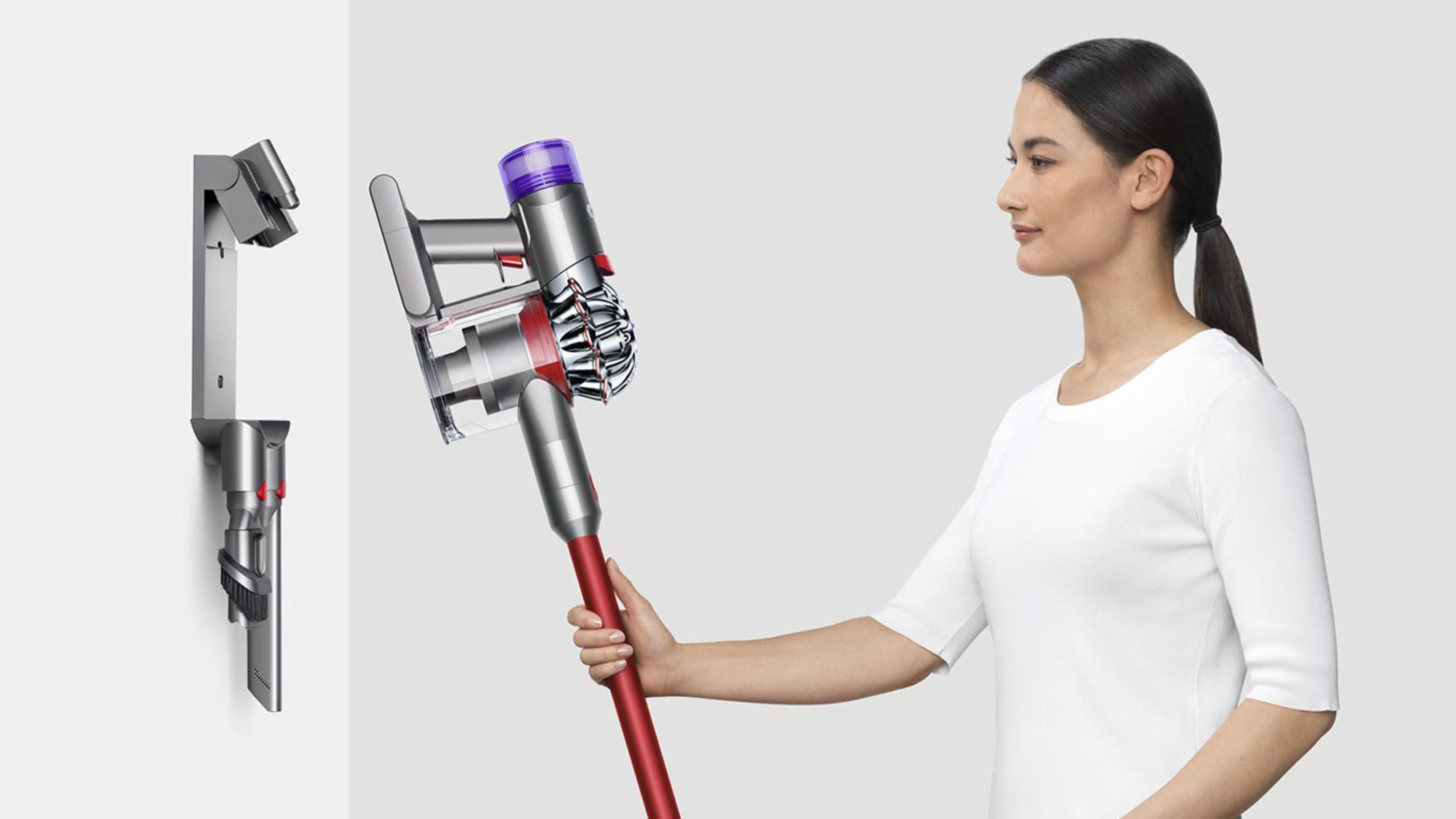 A lady returning the Dyson V8™ vacuum to the charging dock