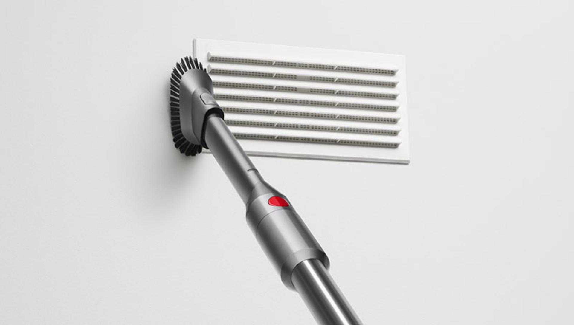 Dyson Micro 1.5kg vacuum cleaning a wall.
