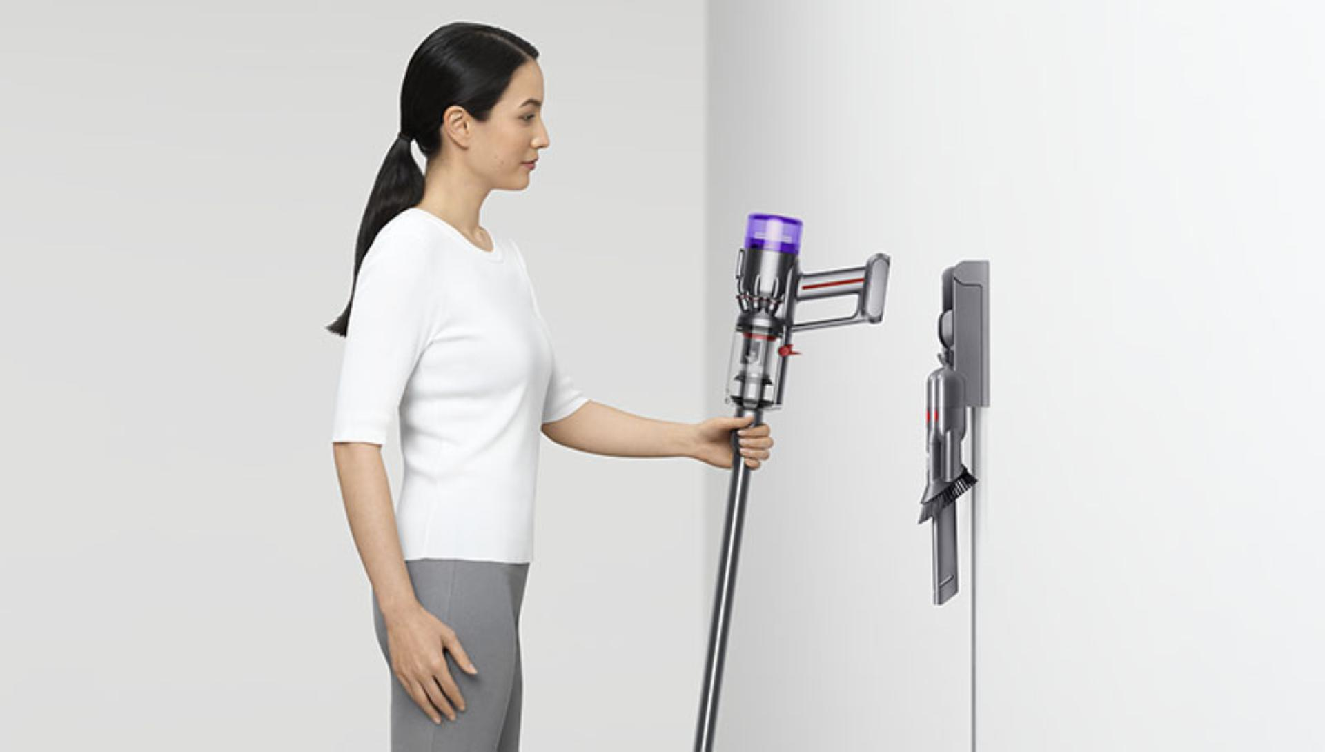 Woman putting a Dyson Micro 1.5kg vacuum into a wall dock