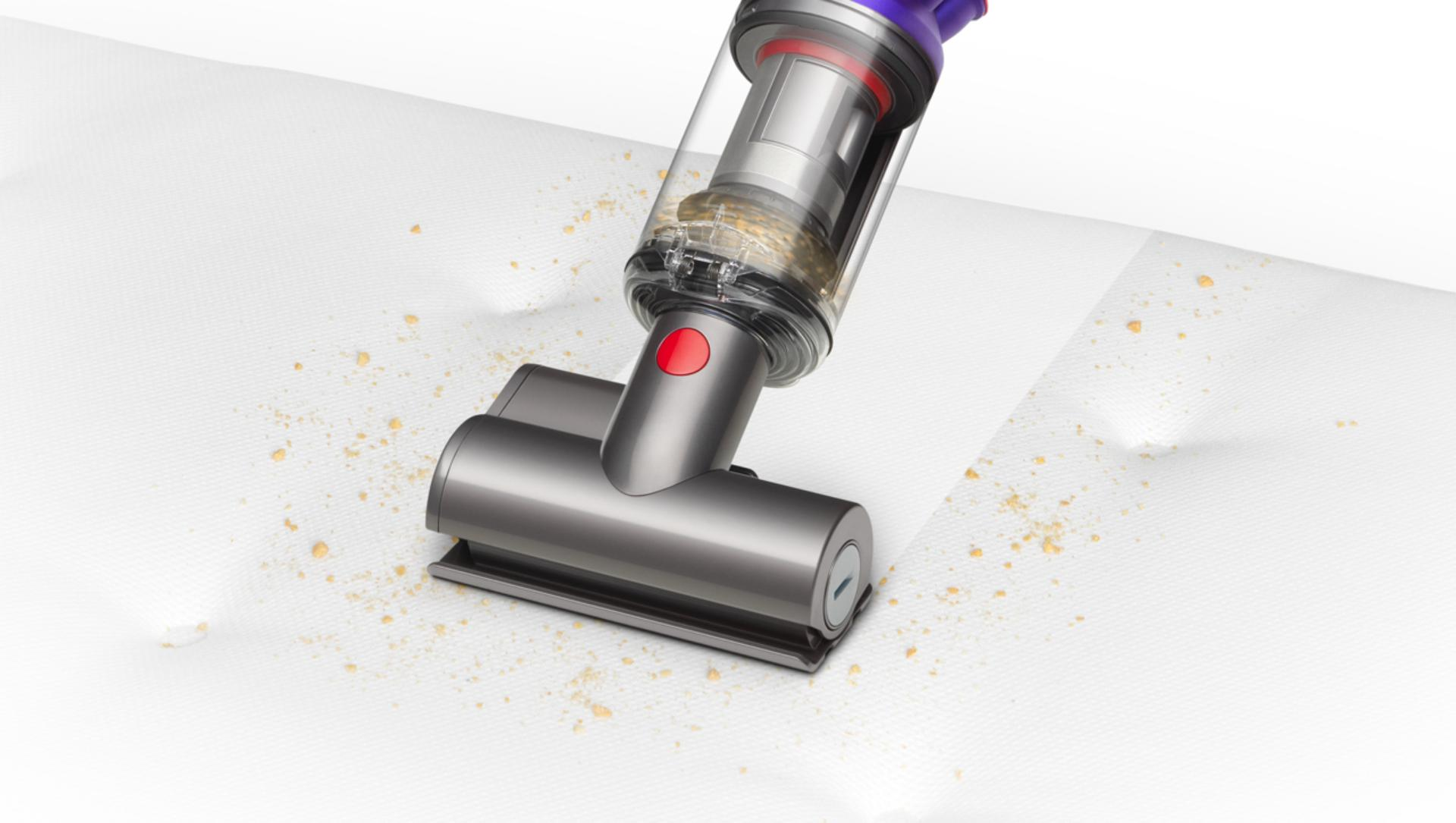 Mini motorised tool being used to clean a mattress.