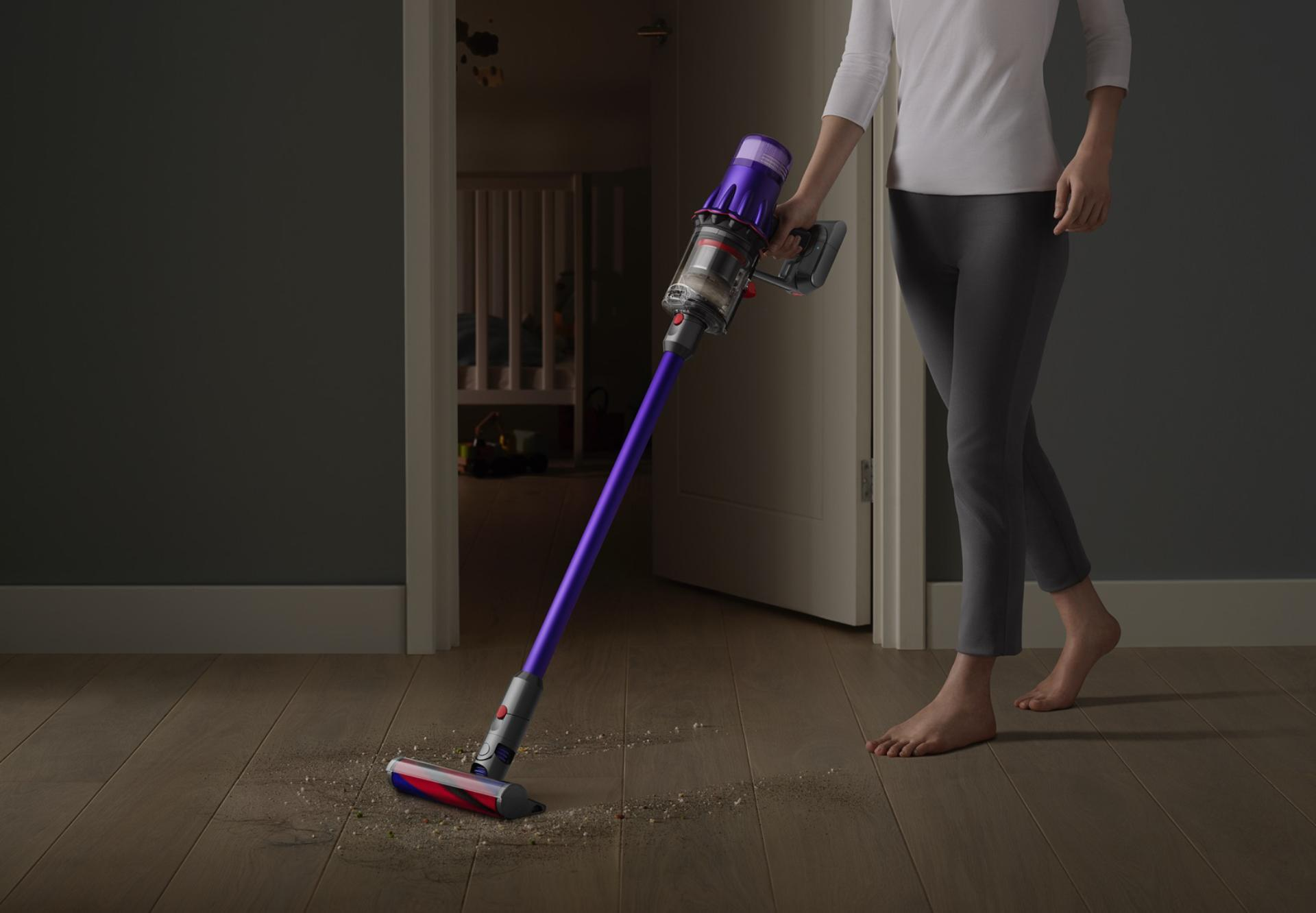 Dyson Digital Slim™ vacuum cleaning a hard floor by a bedroom door.