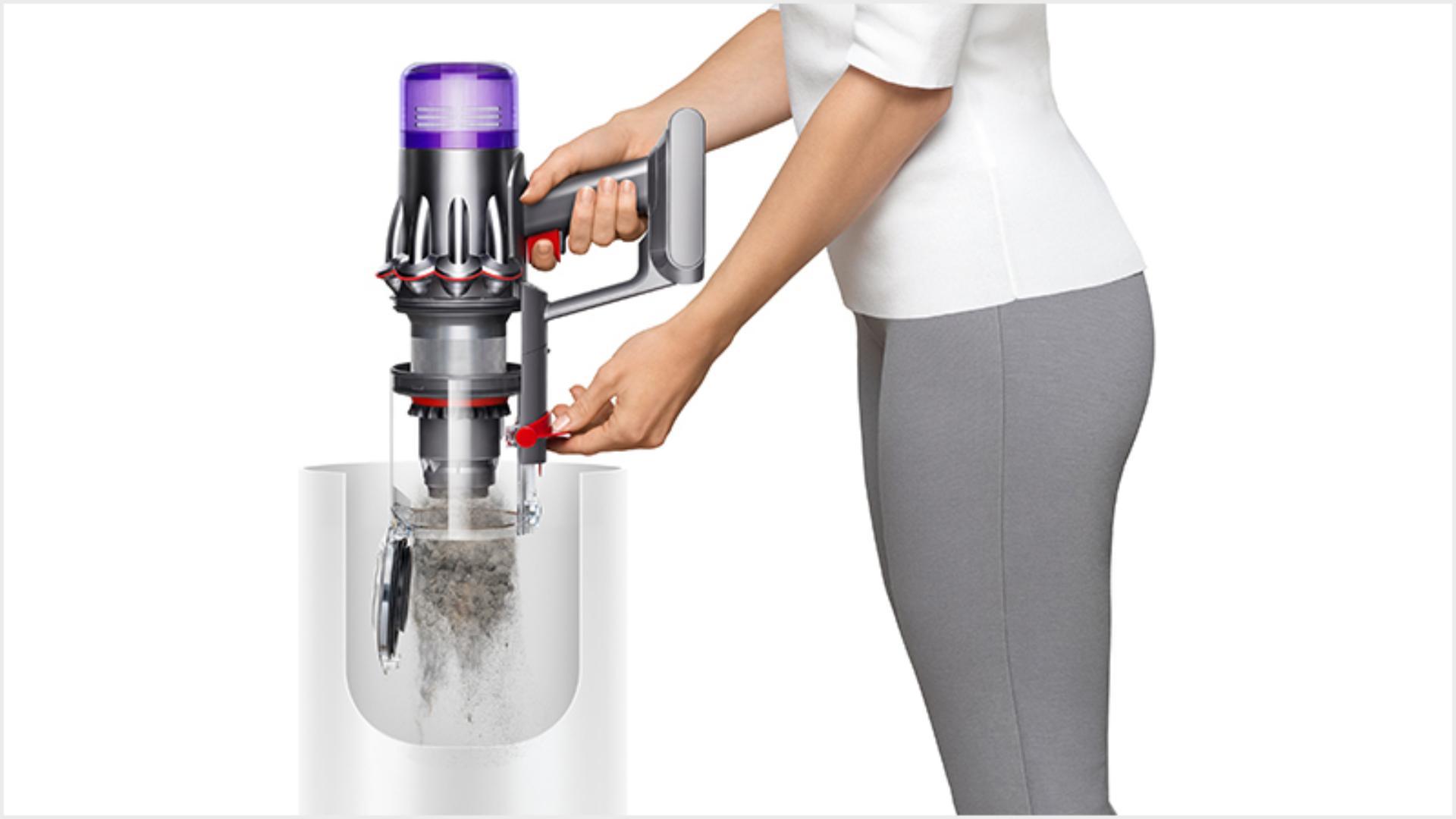 다이슨 디지털 슬림TM 무선 청소기의 먼지를 청소기의 먼지통으로 내보내는 여성