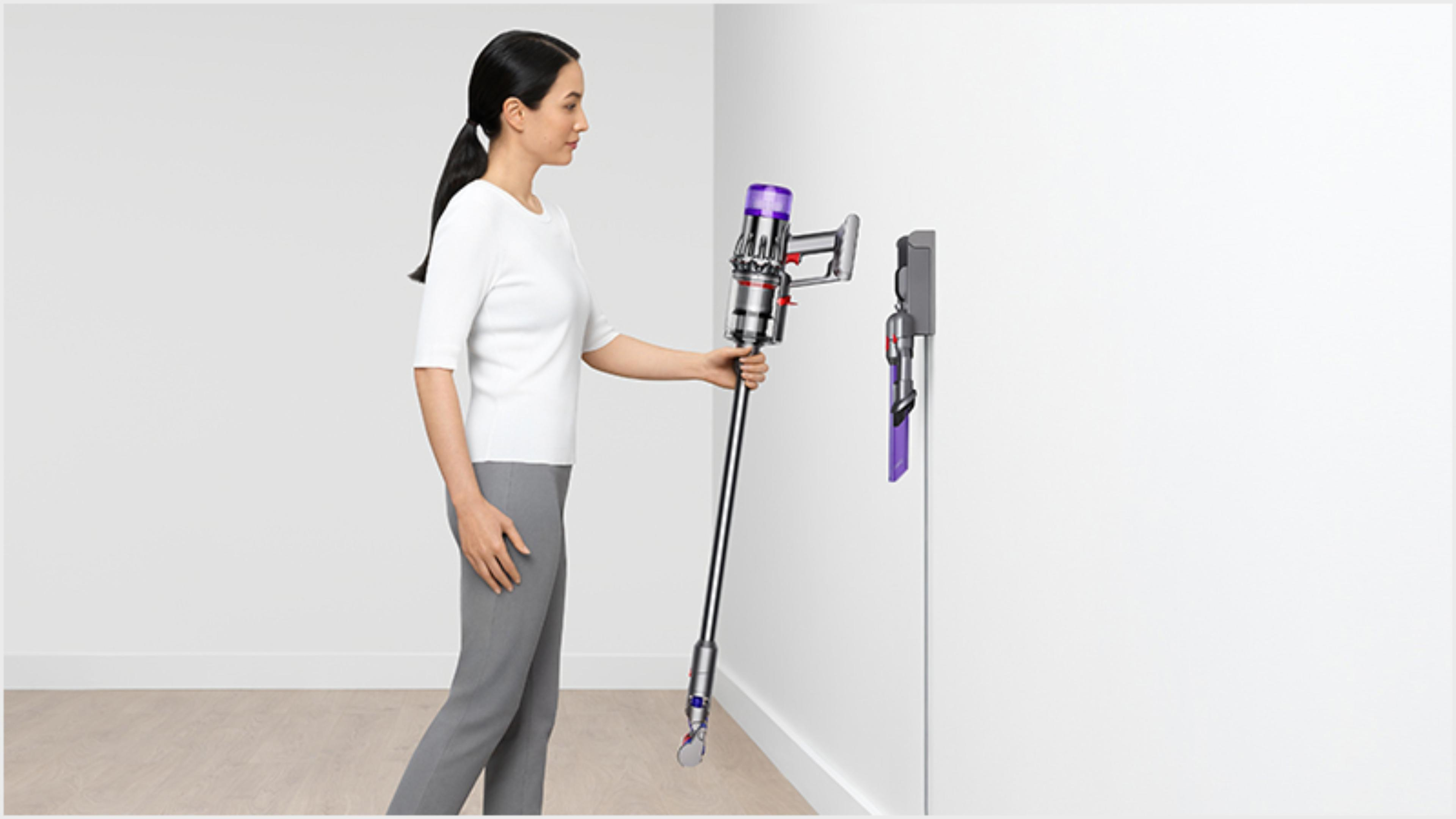 Woman dropping the Dyson Digital Slim vacuum into the wall dock