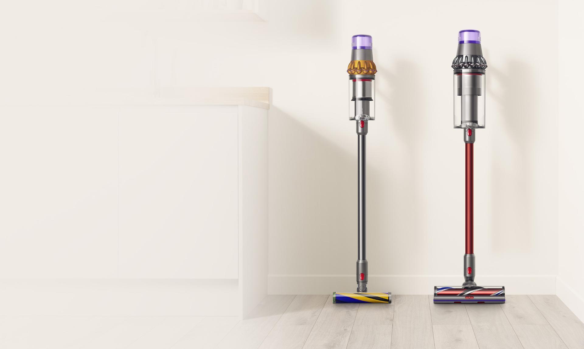 A Dyson V15 Detect cordless vacuum cleaner next to a Dyson Outsize cordless vacuum