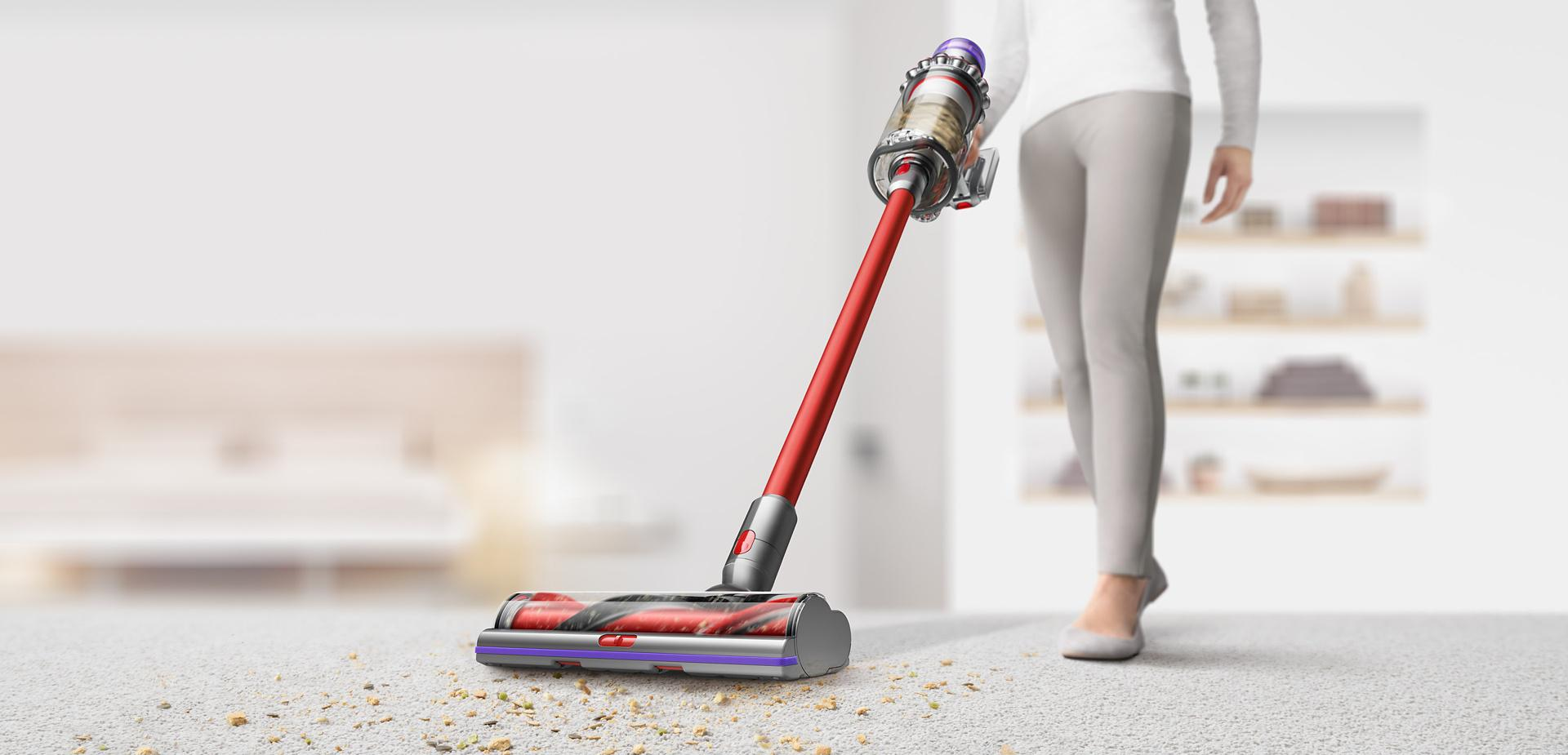 Woman using Dyson Outsize vacuum to clean debris from carpet