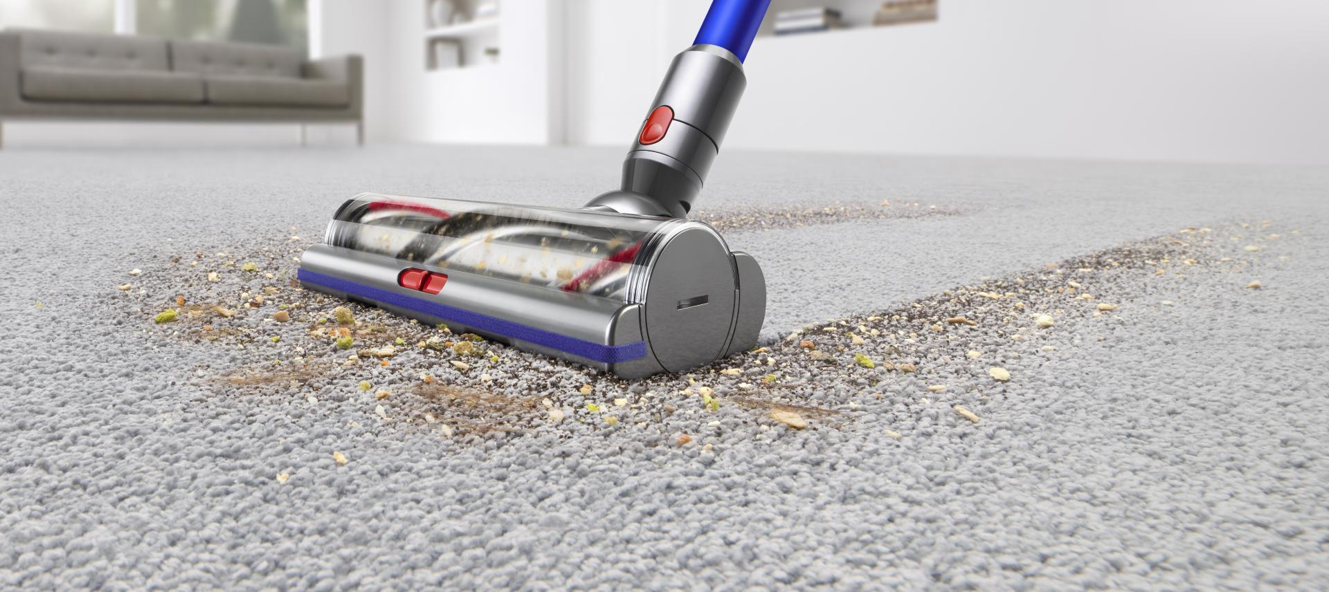 Closeup of vacuum being used on carpet