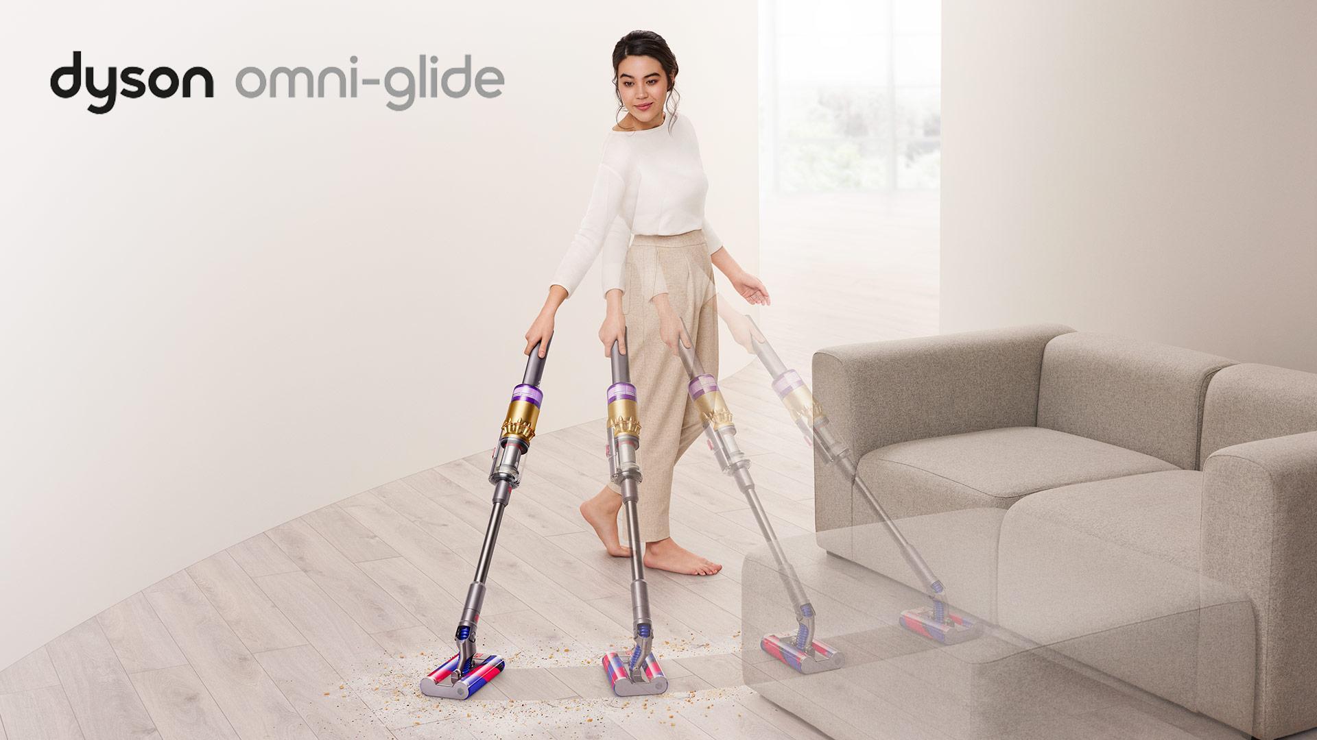 在沙发周围的妇女在沙发周围吸尘的楼层有dyson omni-glide™真空