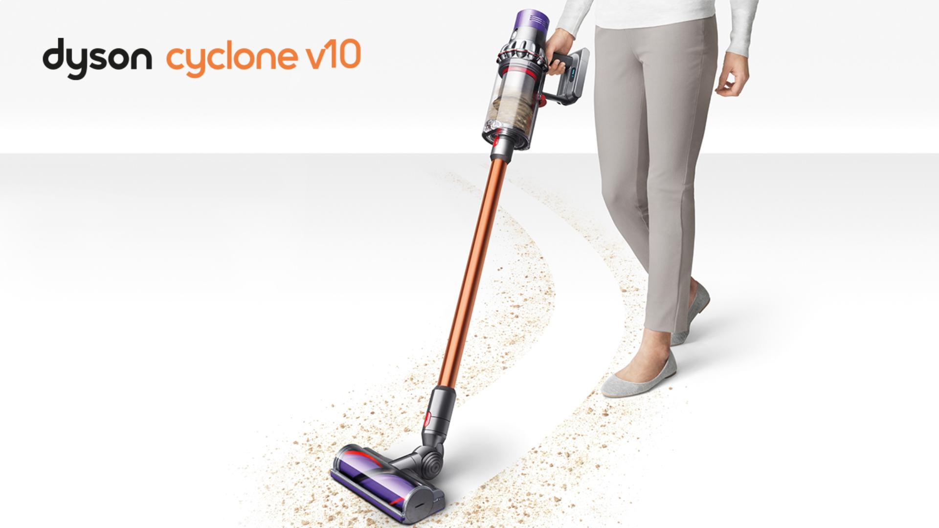 Woman using Dyson cyclone V10 to pick debris up from carpet