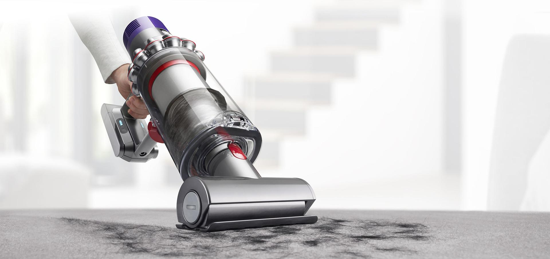 Dyson Cyclone V10™ vacuum in handheld mode cleaning upholstery