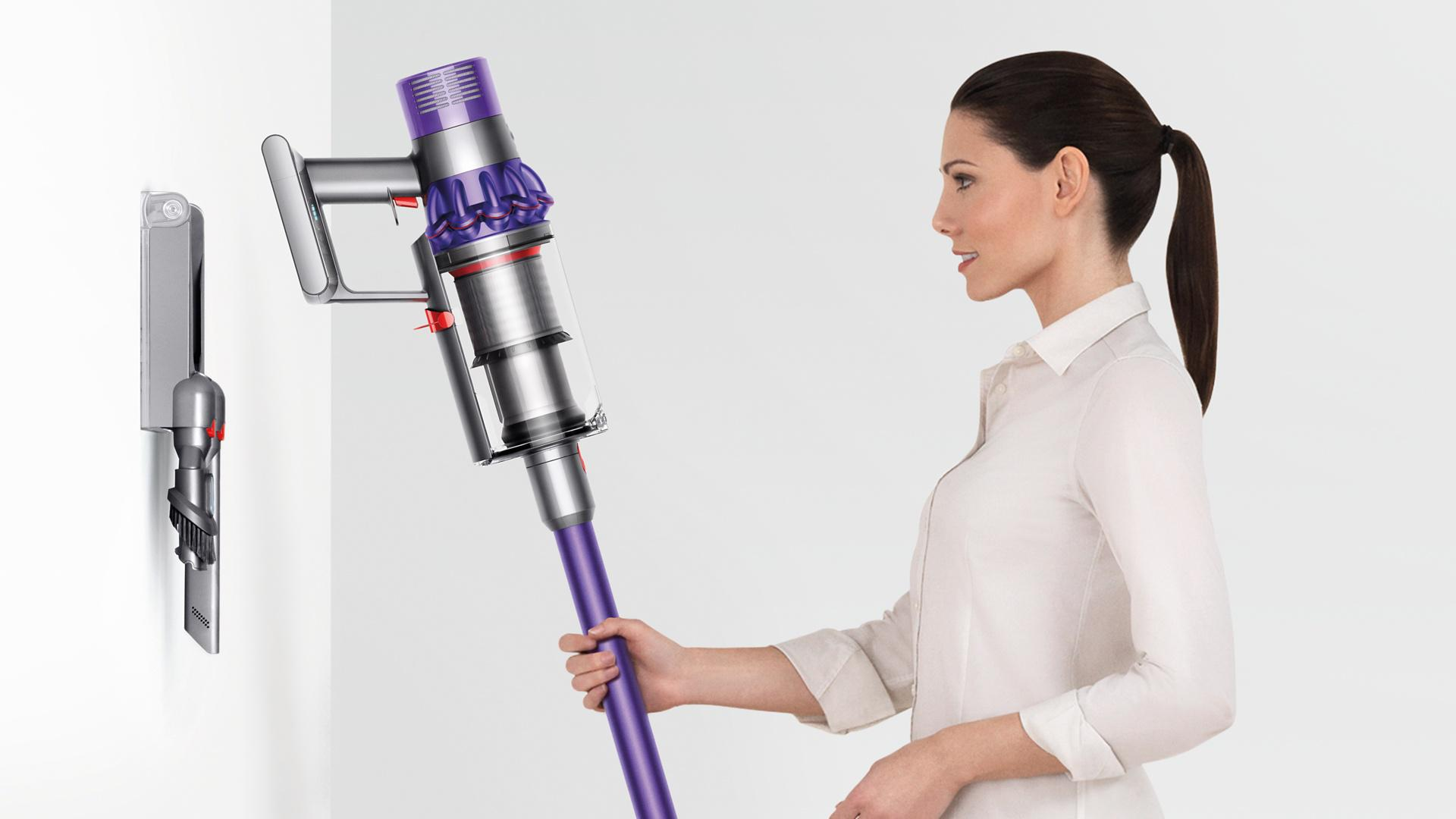 Woman placing the Dyson Cyclone V10 neatly inot docking station
