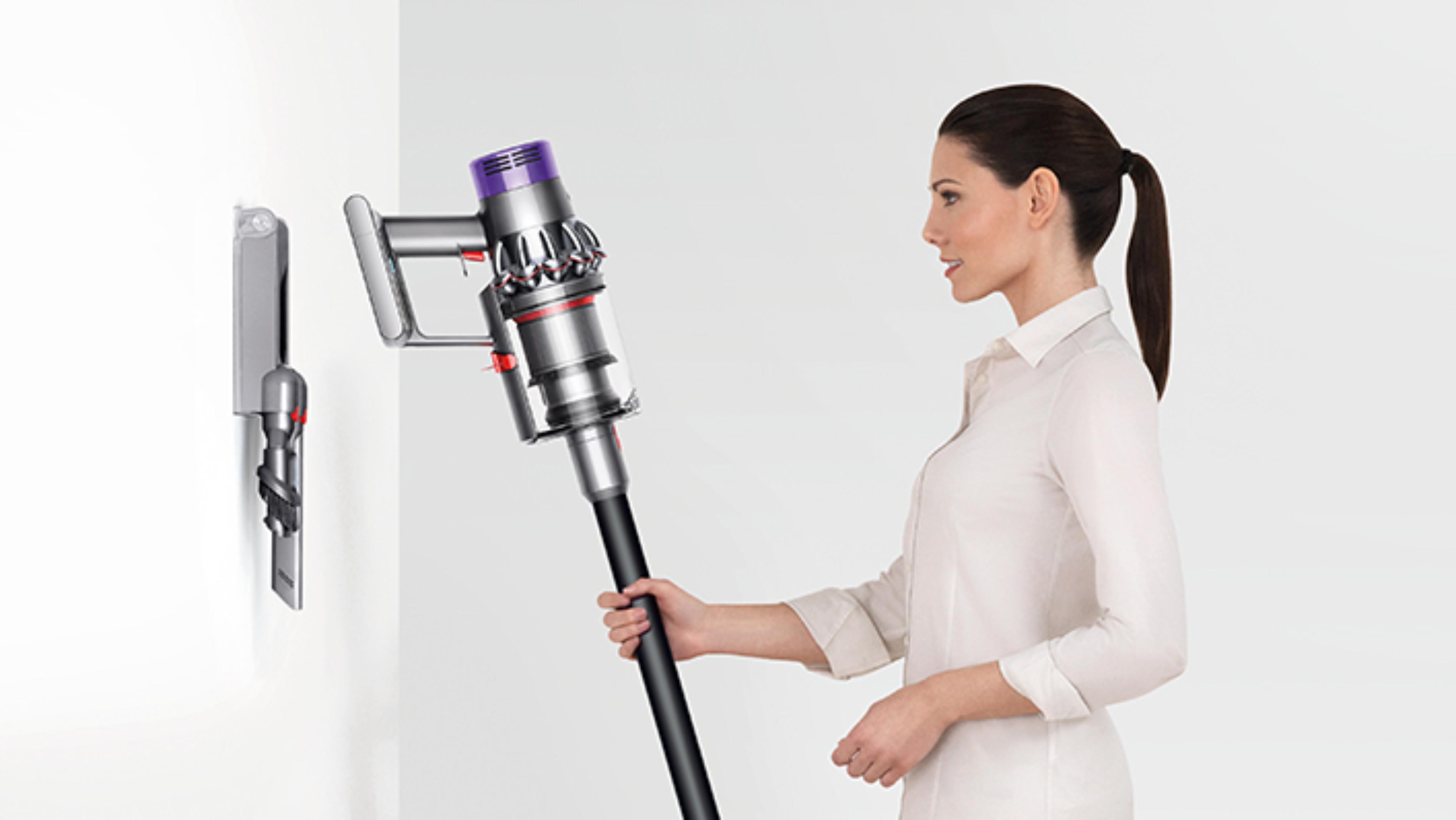 一位女性正在將Dyson Cyclone V10™ 吸塵機放入插入式充電底座