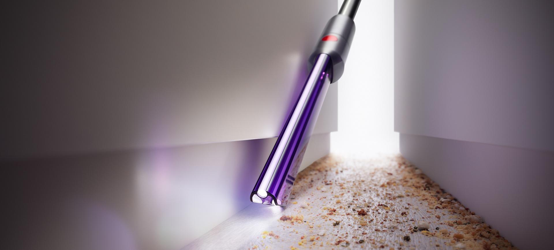 Công cụ hút khe kẽ có đèn chiếu sáng đang làm sạch giữa các ngăn tủ