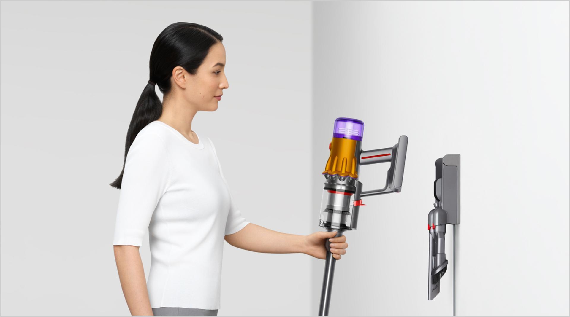 Người phụ nữ đang đặt máy hút bụi Dyson vào trong đế sạc gắn tường