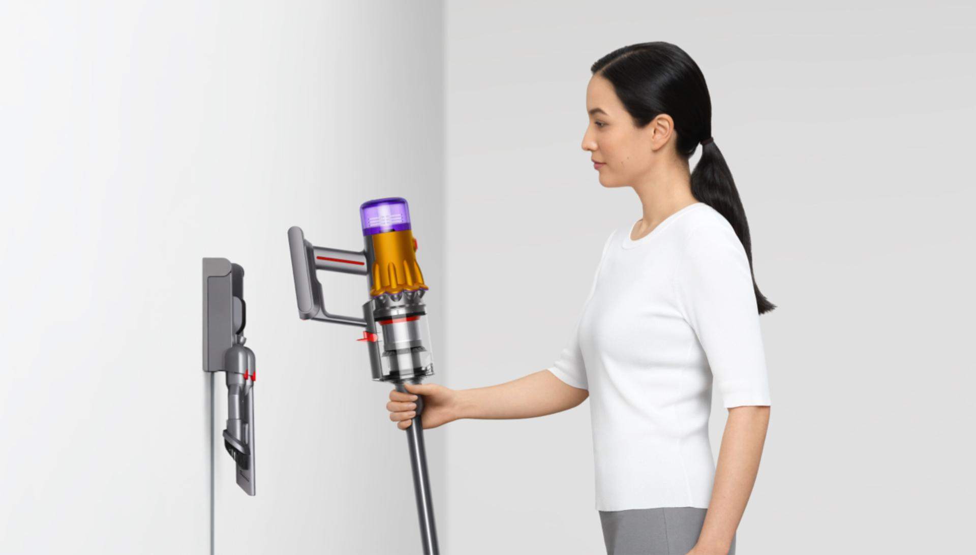 Woman placing the Dyson V15 Detect vacuum on the wall dock