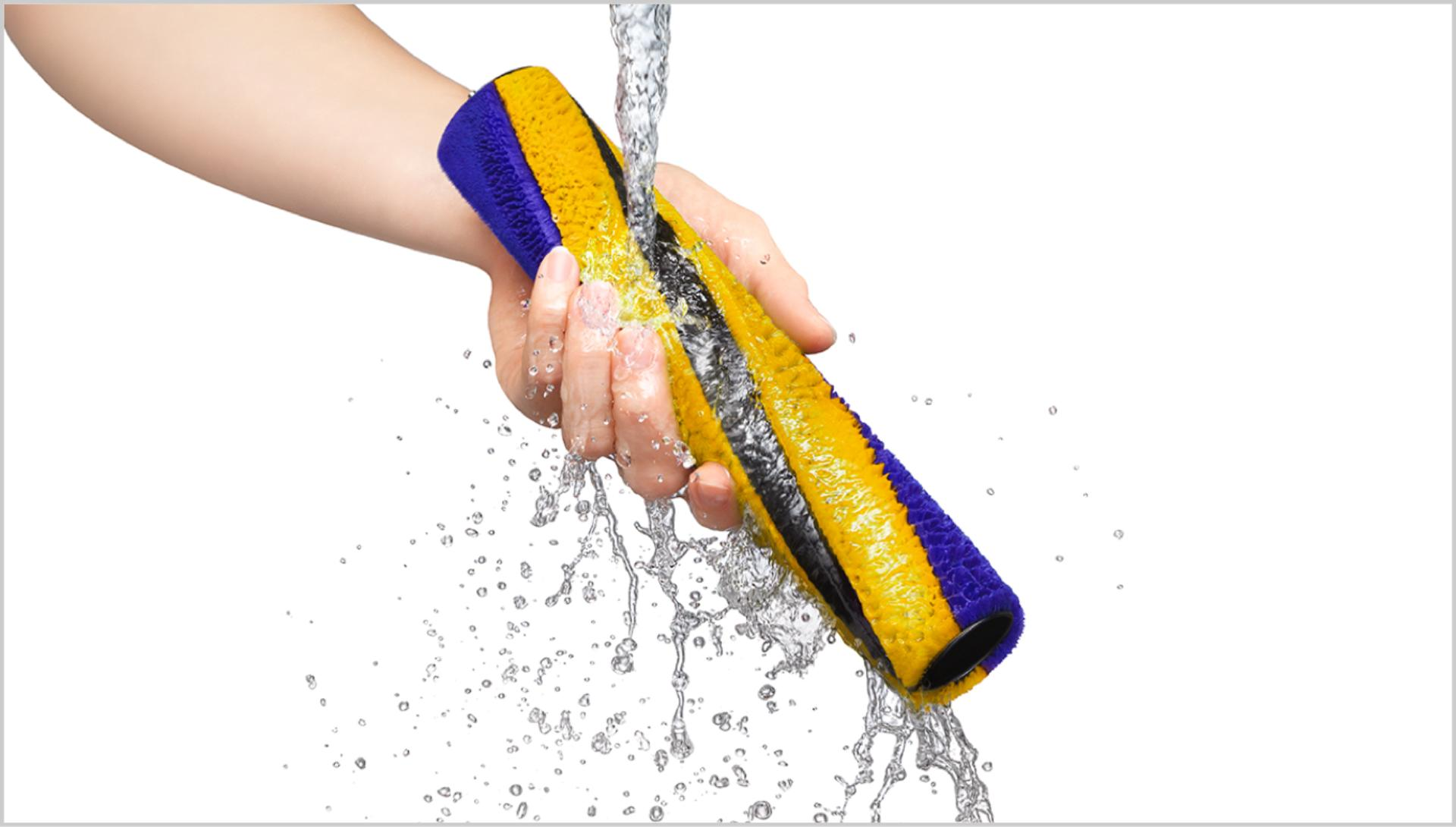 Person washing the Fluffy brush bar under a tap