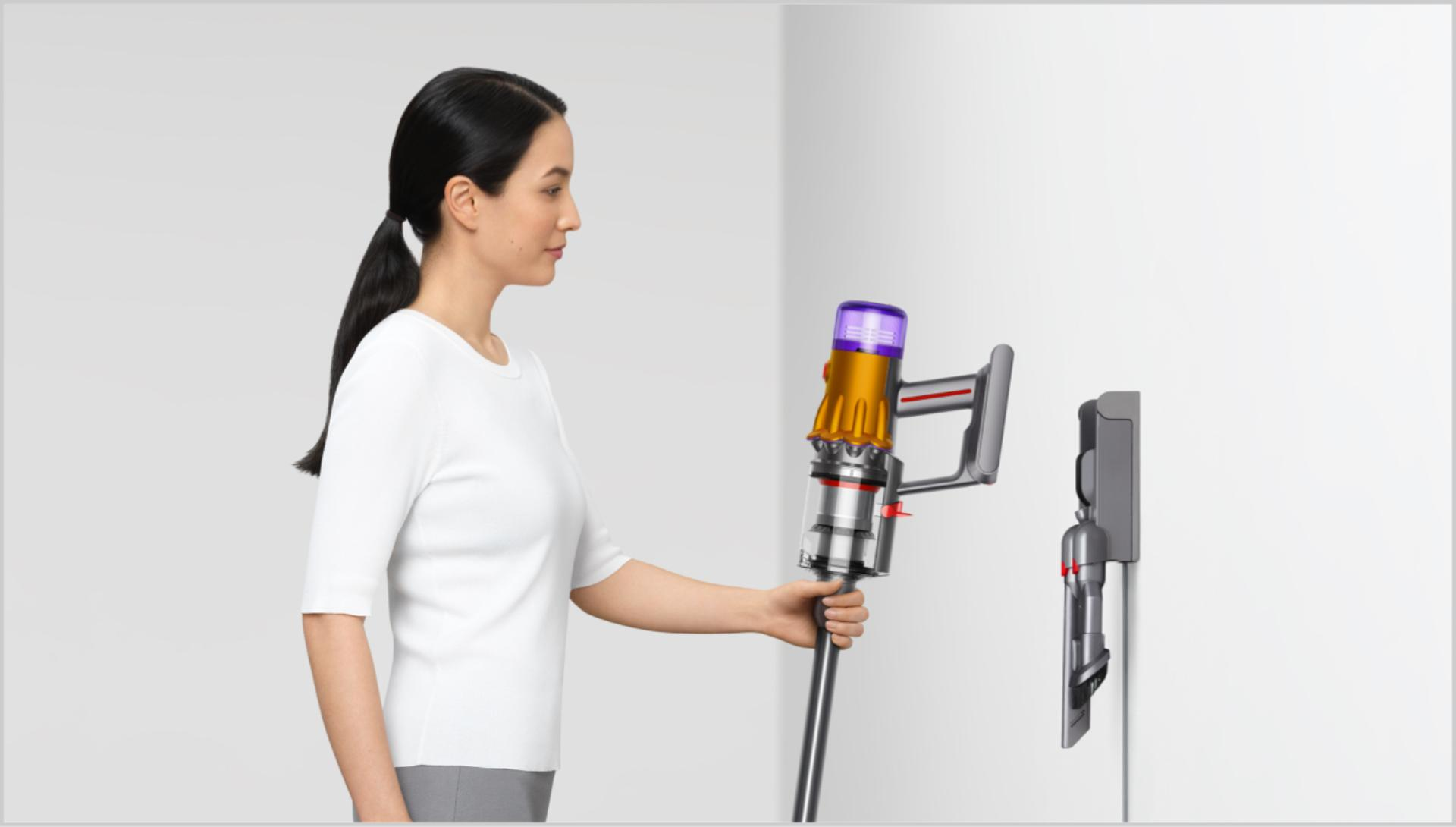 Woman placing Dyson vacuum into the wall dock