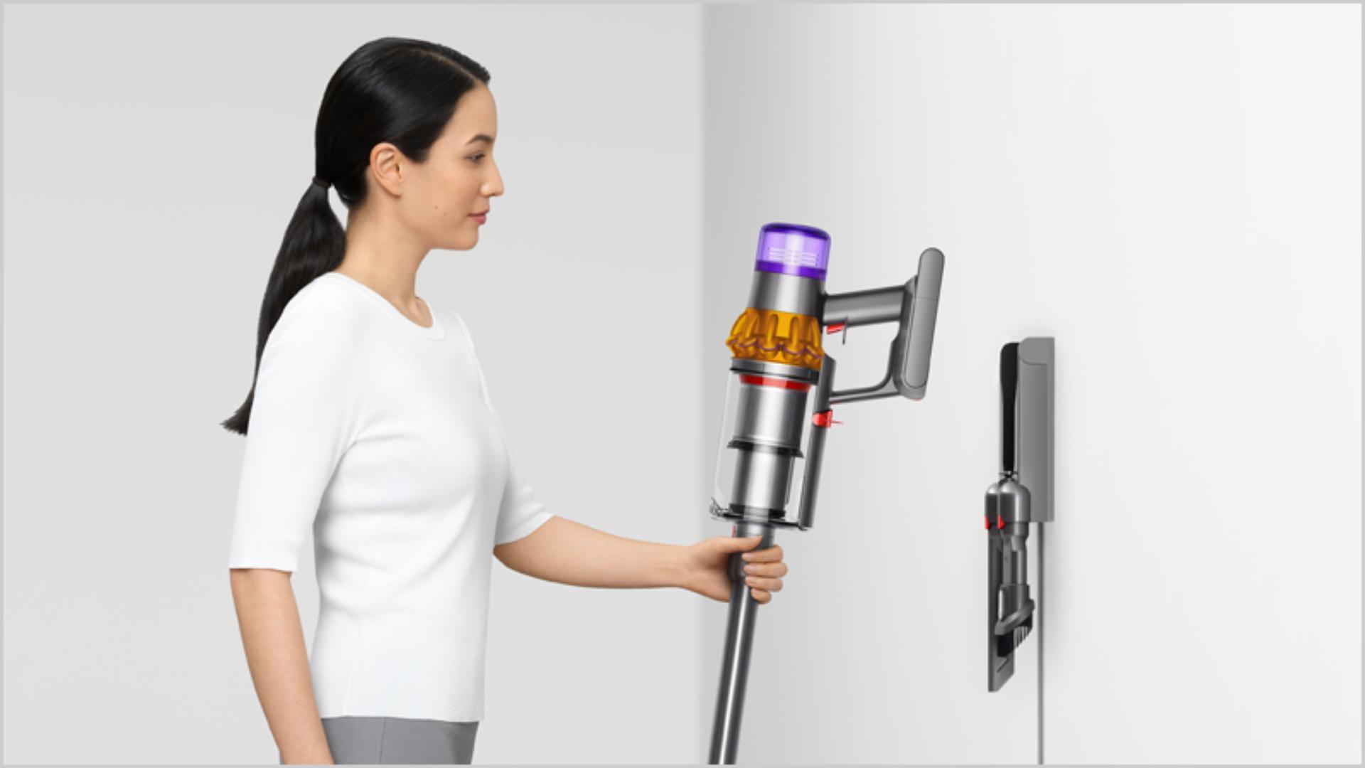 Dyson kablosuz süpürgeyi duvar ünitesine yerleştiren kadın