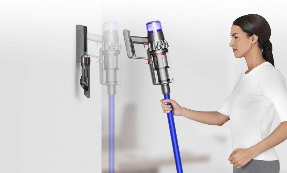 Dyson V15 Detect kablosuz süpürgesini duvar askı ünitesine yerleştiren kadın