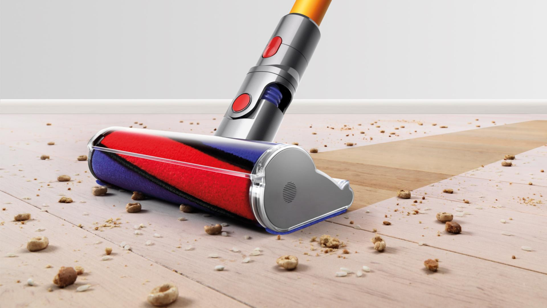 Close up of Dyson brush bar picking up debris from hard floor.