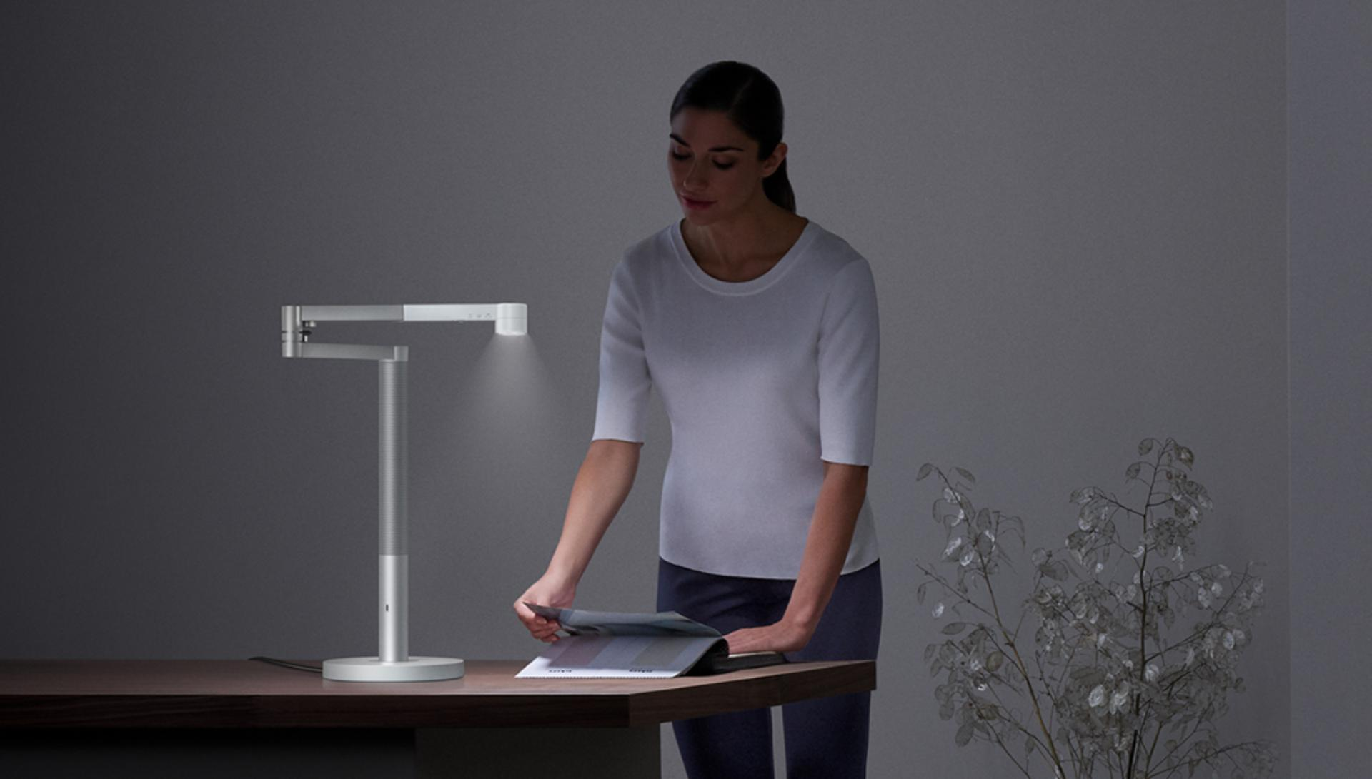 Woman viewing papers under bright light from the Dyson Lightcycle Morph light