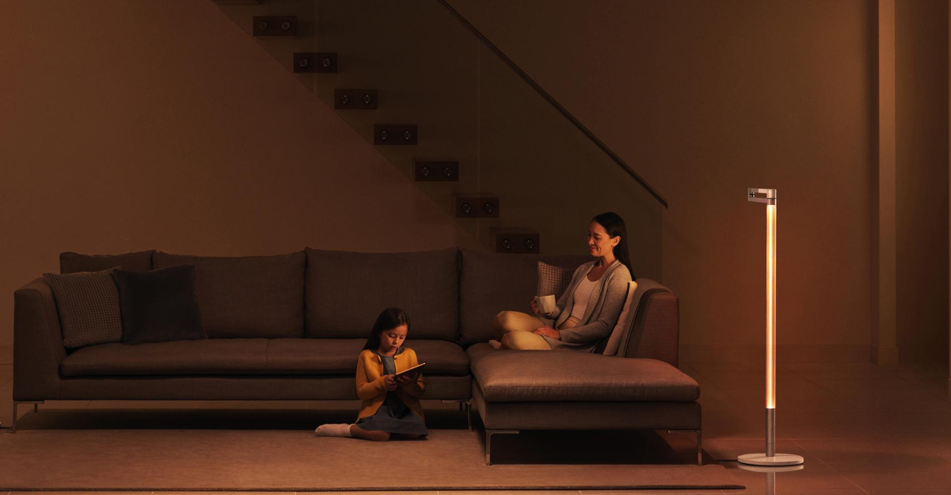 Family relaxing in soothing ambient light from the the Dyson Lightcycle Morph light