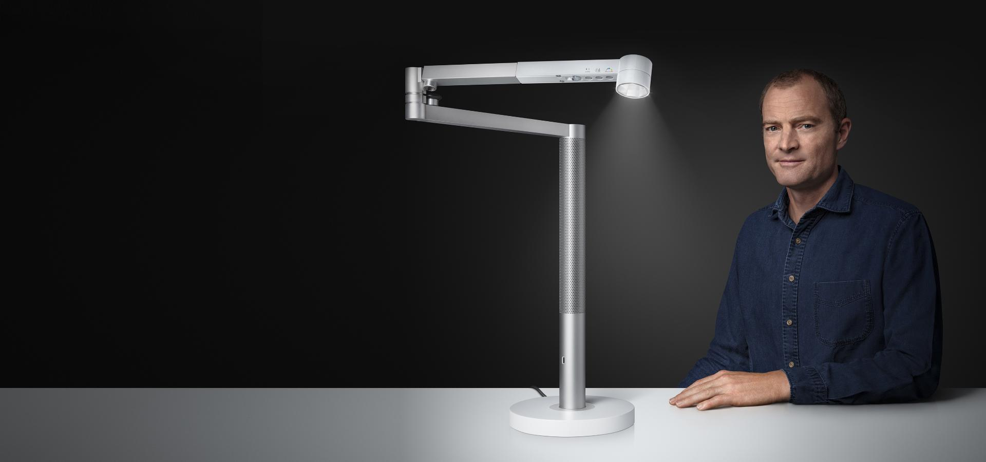 Jake Dyson sitting next to the Dyson Lightcycle Morph light