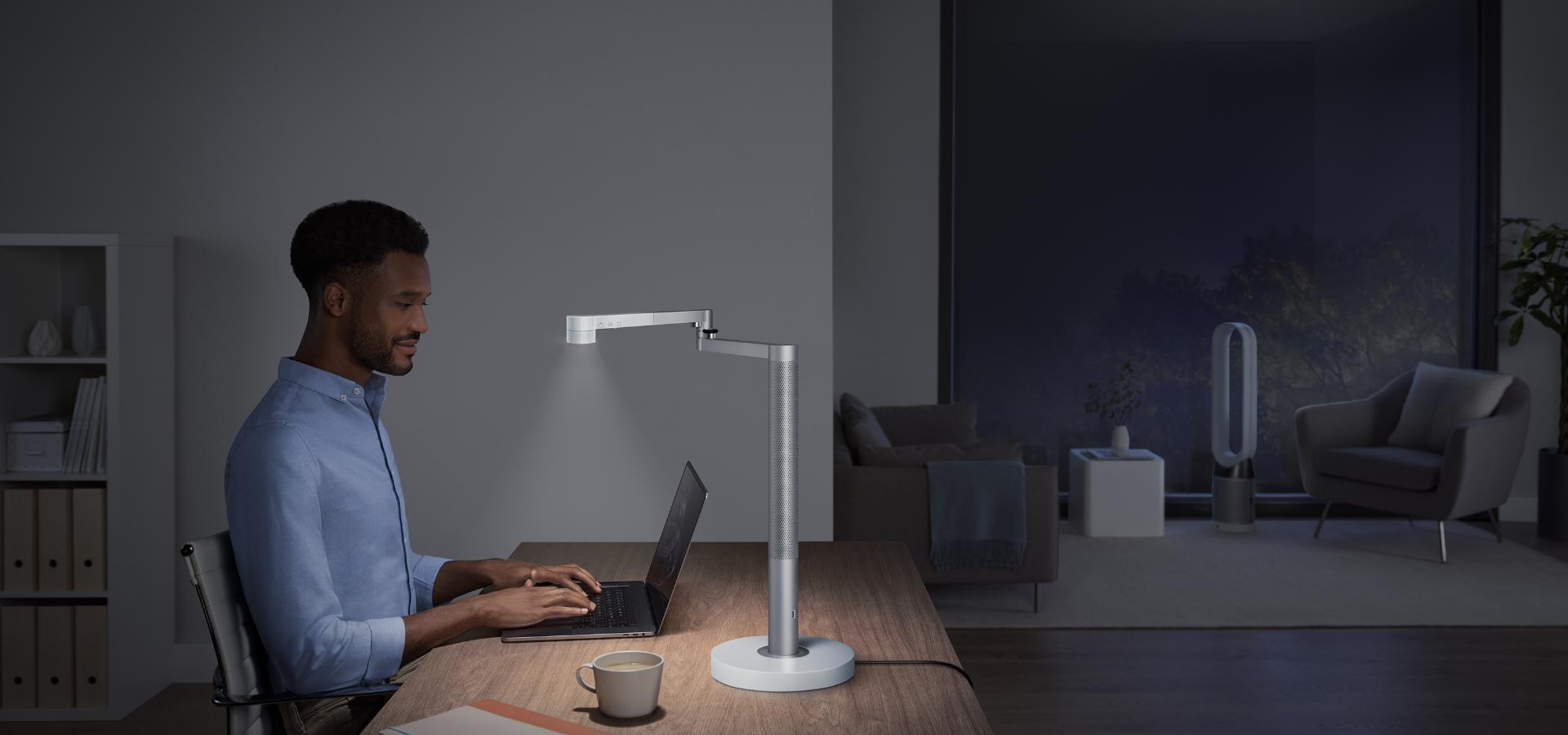 Man working at a desk illumninated by the  Dyson Lightcycle Morph light