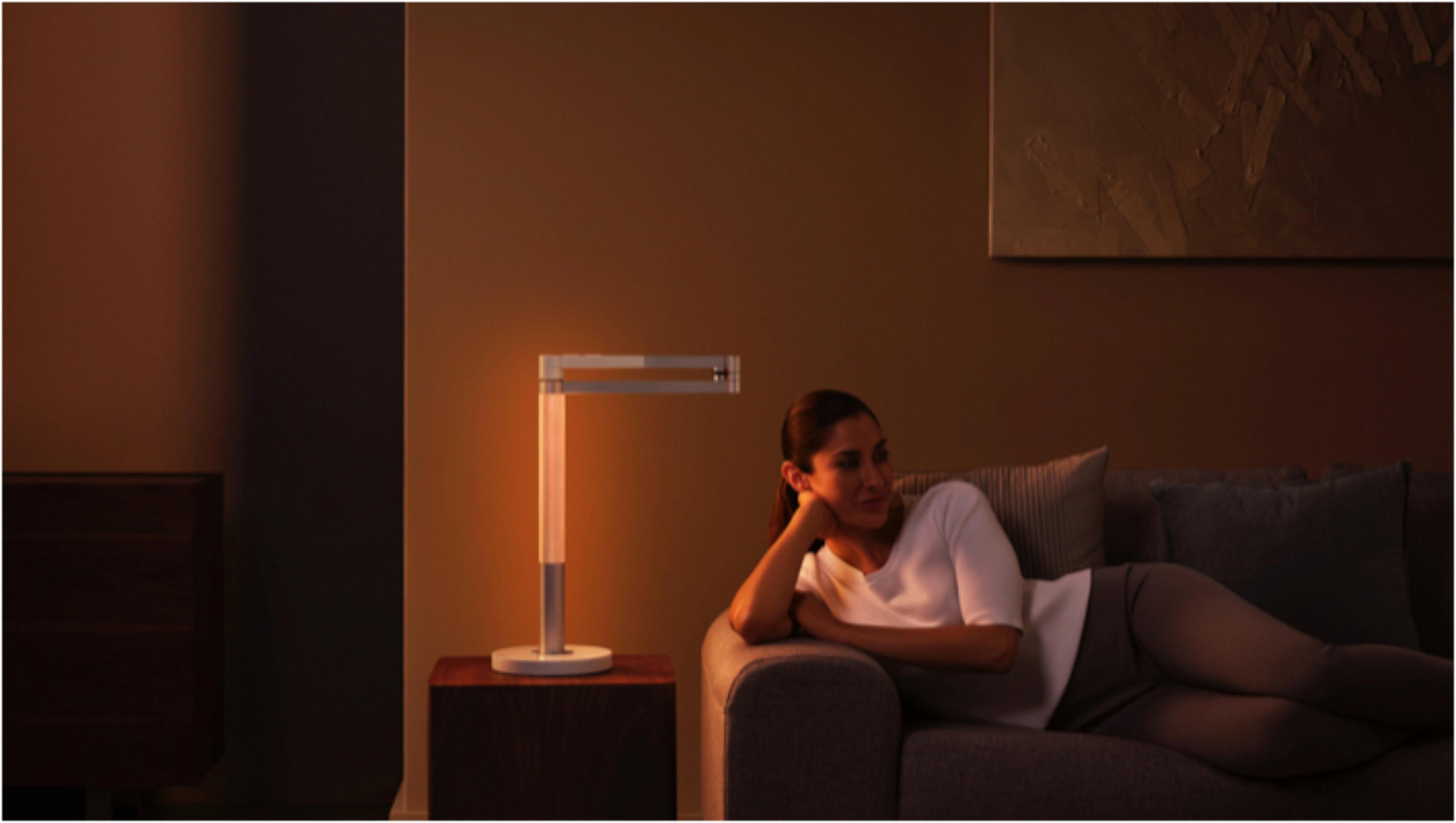 在Dyson Lightcycle Morph燈具環境光狀態下,有一位在美麗的橙色光芒中放鬆自若的女士