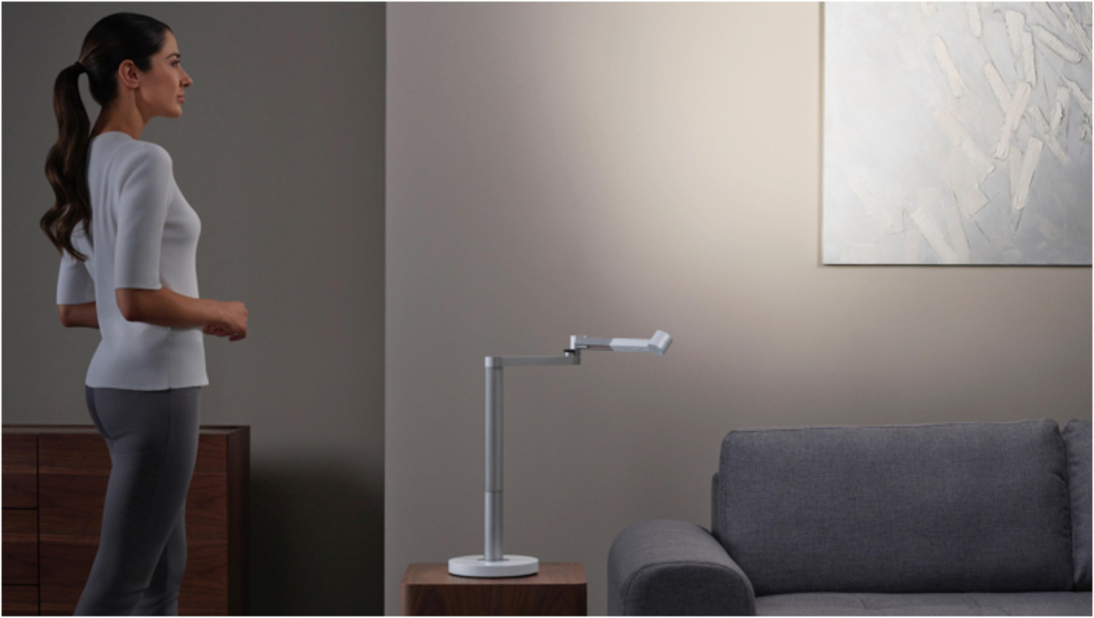 在Dyson Lightcycle Morph燈具功能光狀態下觀賞藝術品的女士