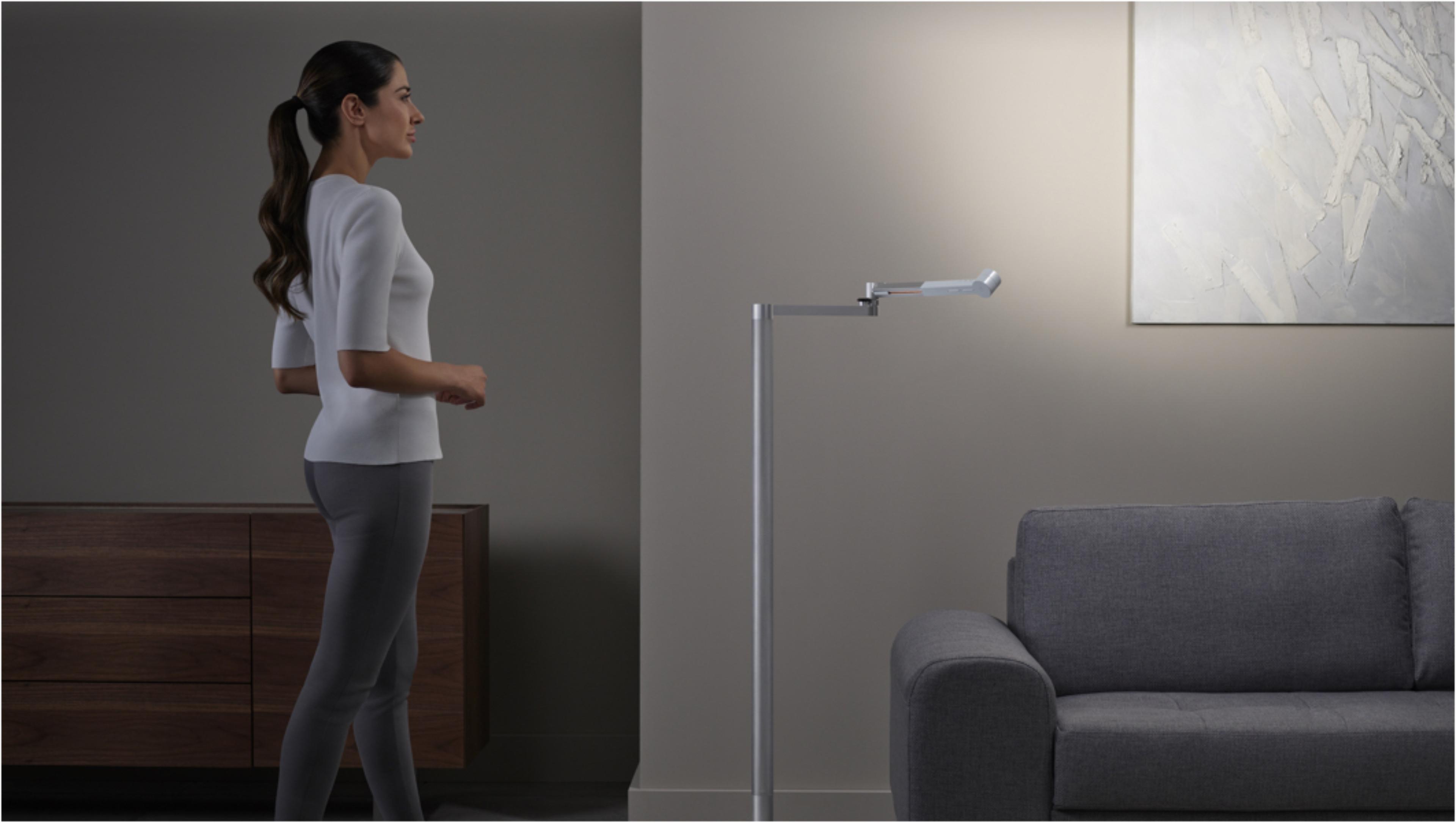 ผู้หญิงกำลังจ้องมองผลงานศิลปะที่มีแสงแบบ Feature จากโคมไฟ Dyson Lightcycle Morph ตกกระทบ