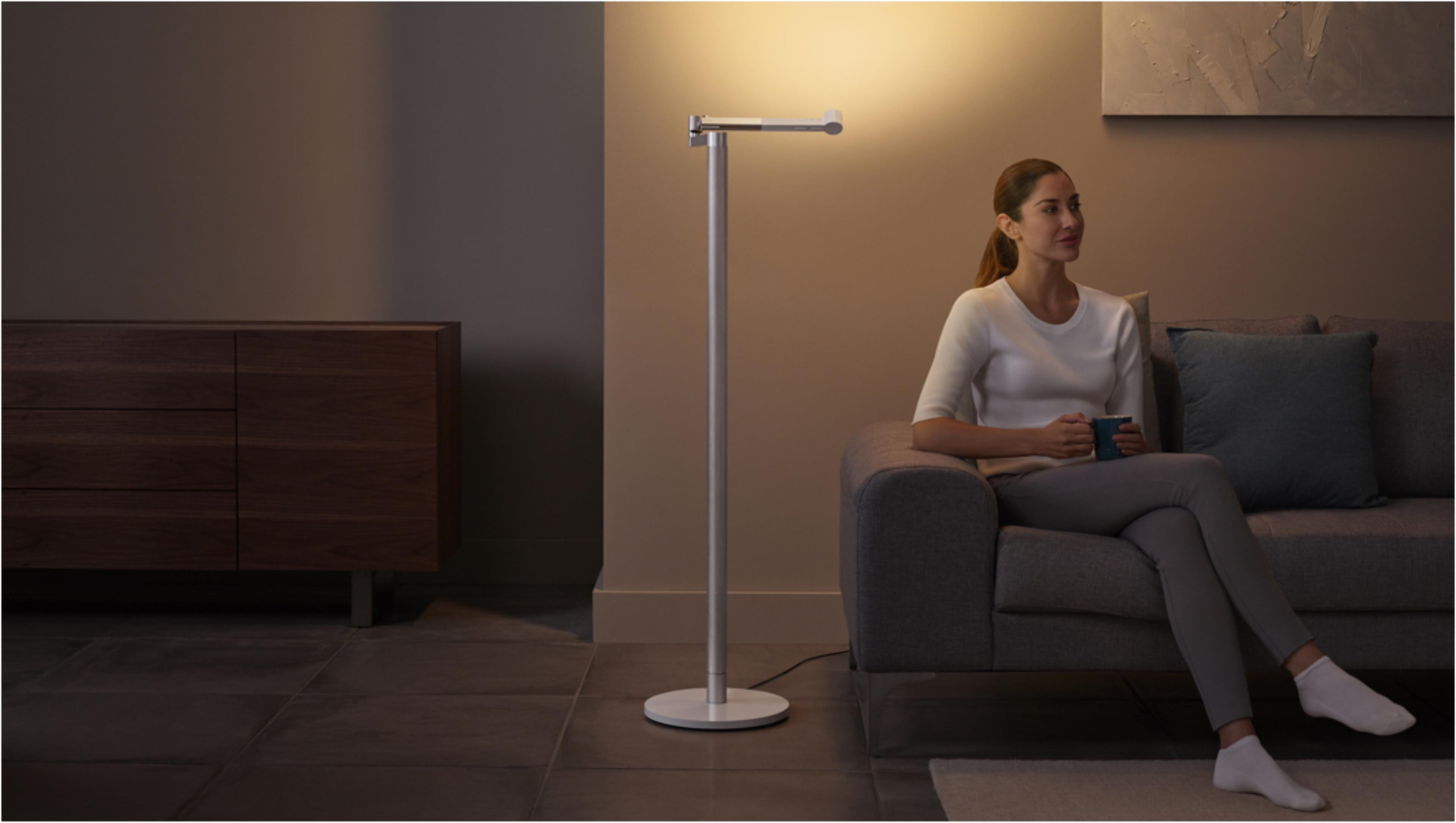 ผู้หญิงกำลังพักผ่อนอยู่ใต้แสงไฟแบบ Indirect ที่ดูดีมีสไตล์จากโคมไฟ Dyson Lightcycle Morph
