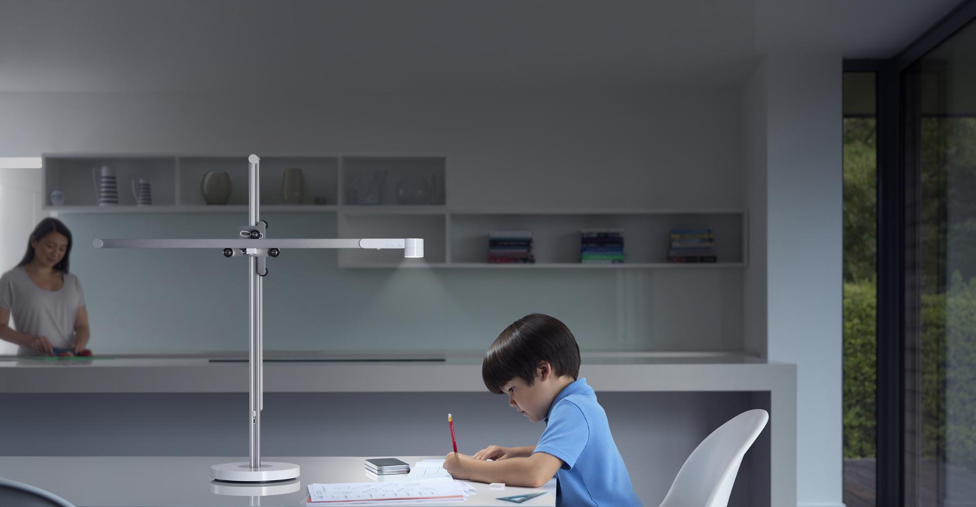 강력한 다이슨 라이트 사이클 테스크 조명 아래 책상에서 학습 중인 소년과 배경의 어머니