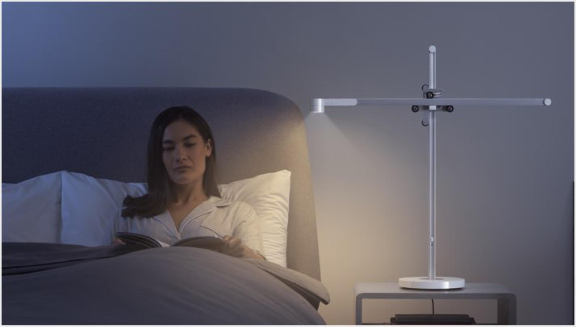 다이슨 라이트 사이클 테스크 조명을 켜고 침대에서 휴식 중인 여성