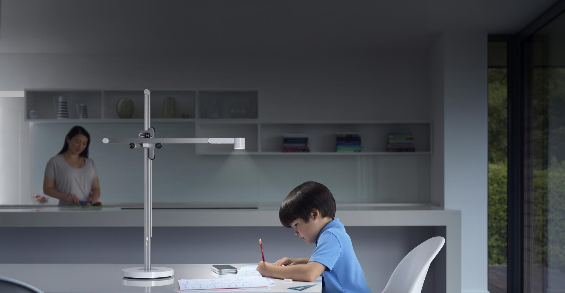 Boy studying at desk under powerful Dyson Lightcycle task light with mother in the background