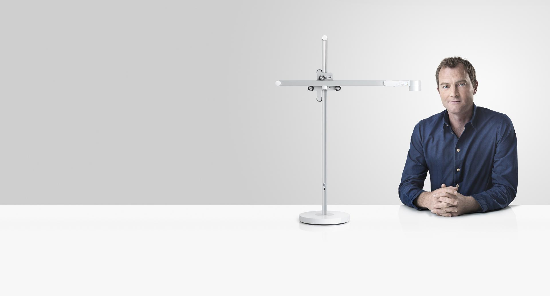 Jake Dyson sitting next to the Dyson Lightcycle task light