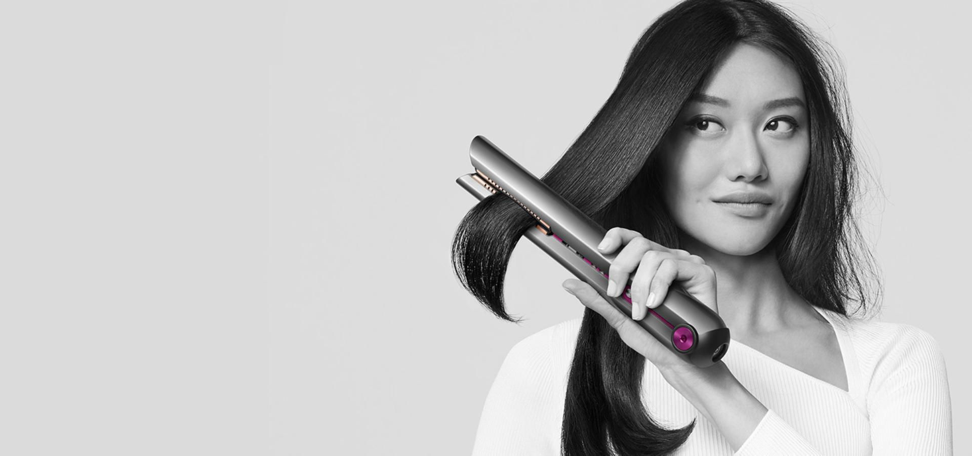 Woman achieving beautifully straight hair with the Dyson Corrale™ straightener