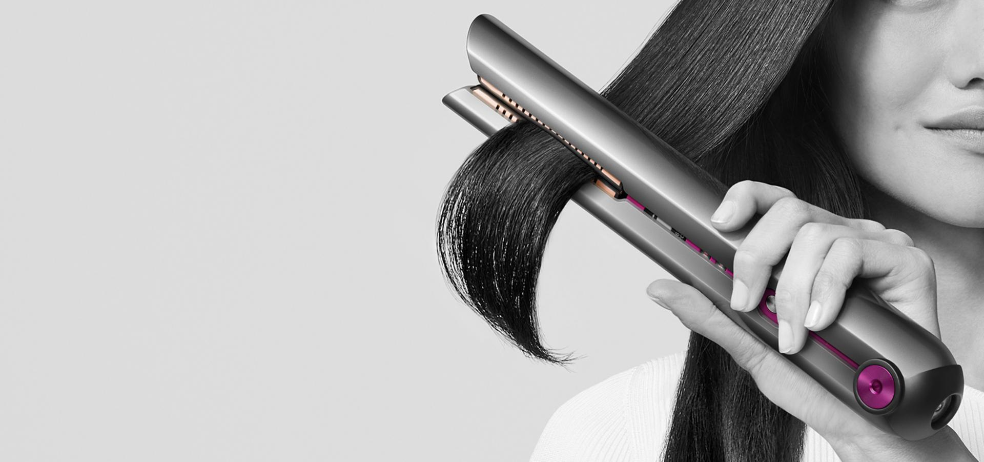 Woman straightening her hair with the Dyson Corrale straightener