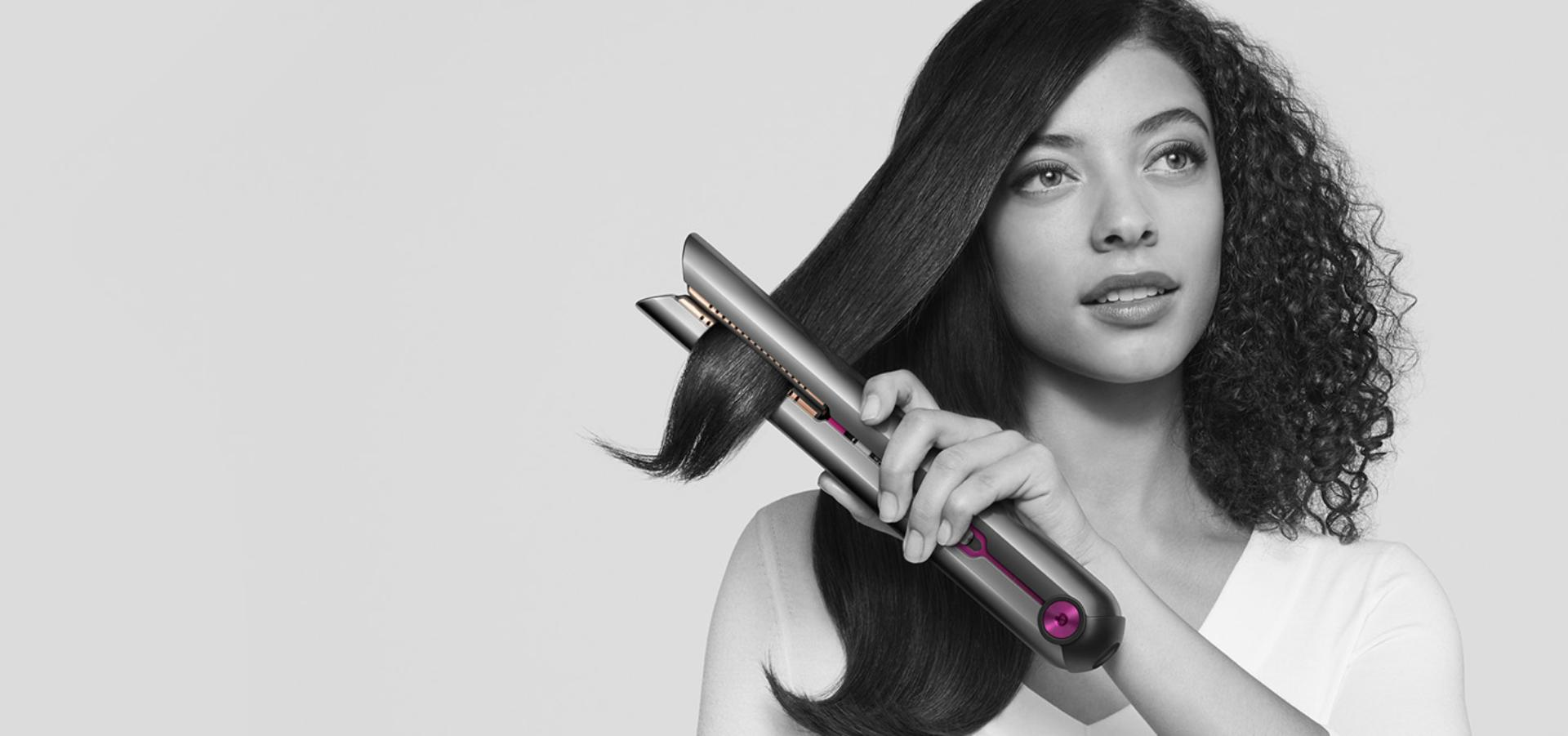 Woman straightening her hair with the Dyson Corrale™ straightener