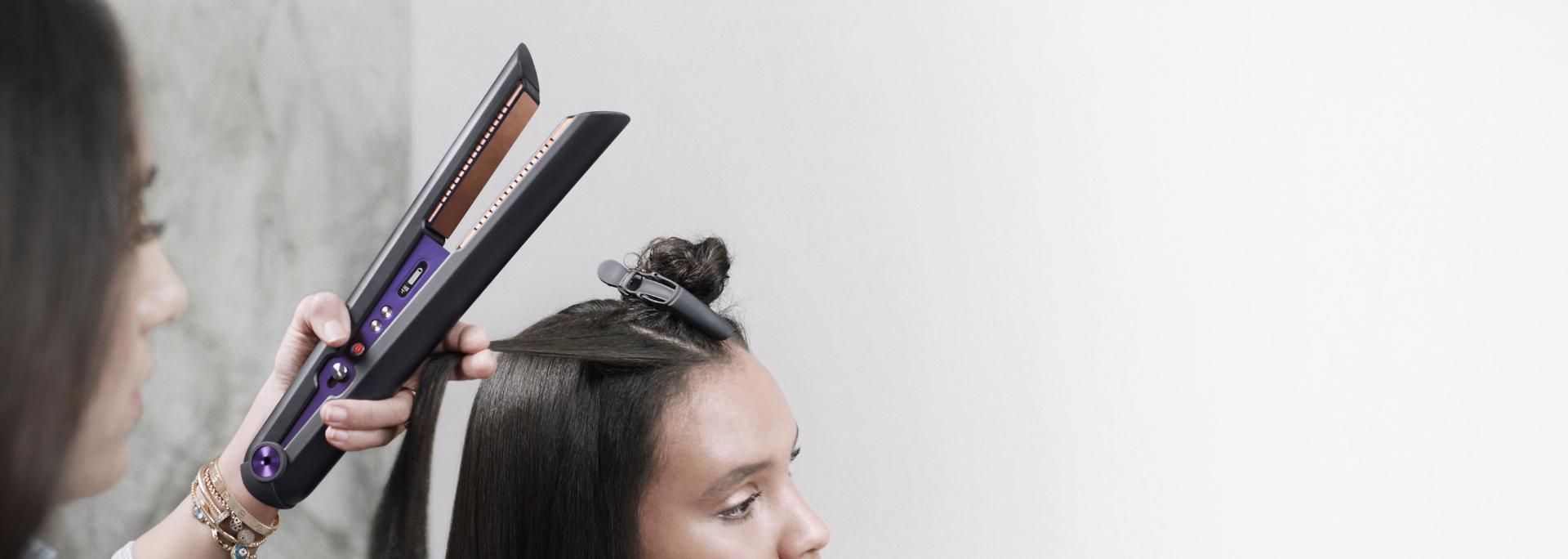 صورة مُقرَّبة من مُصفّفة شعر محترفة تستخدم جهاز تمليس الشعر Dyson Corrale