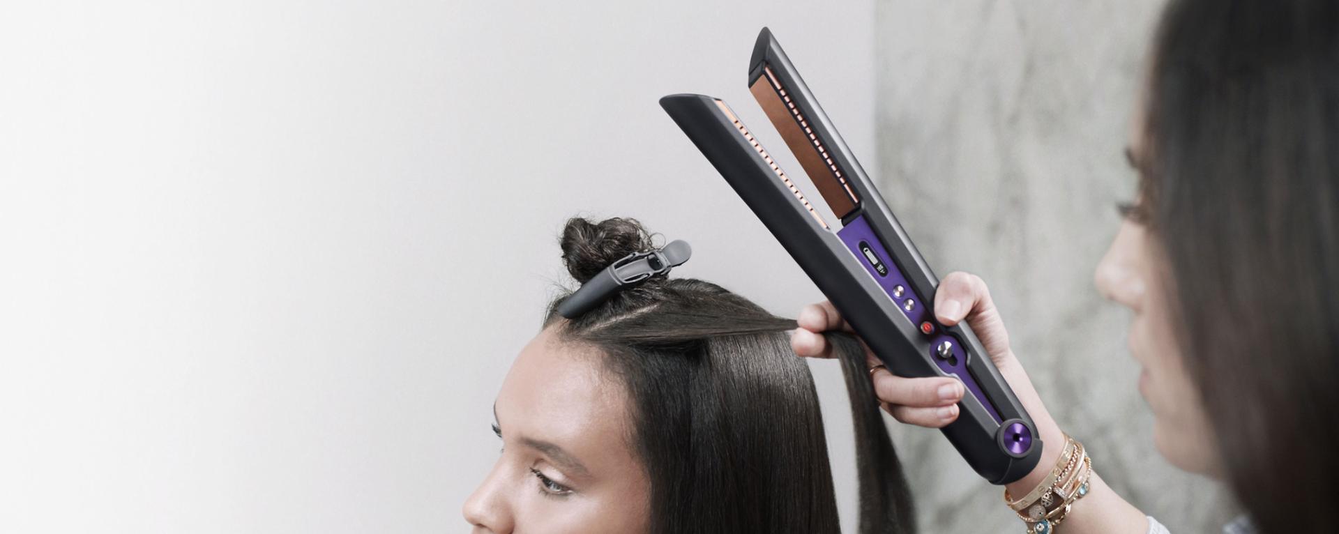 Közelkép a Dyson Corrale hajvasalót használó professzionális stylistról