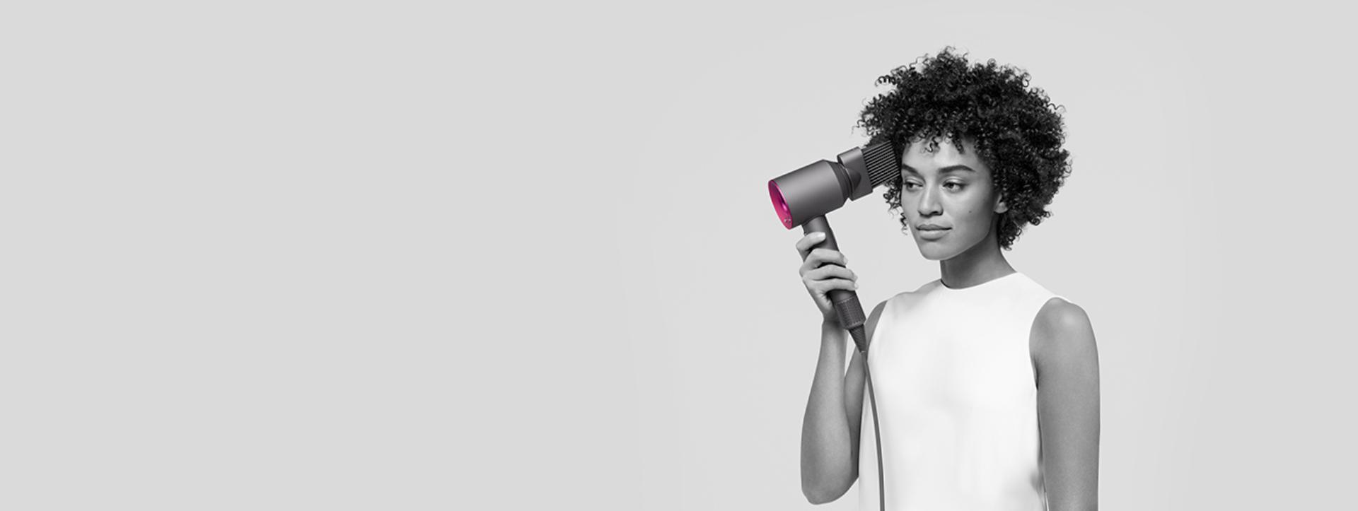 kobieta modelująca włosy przy użyciu suszarki Dyson Supersonic wraz z nasadką grzebienia z szerokimi zębami