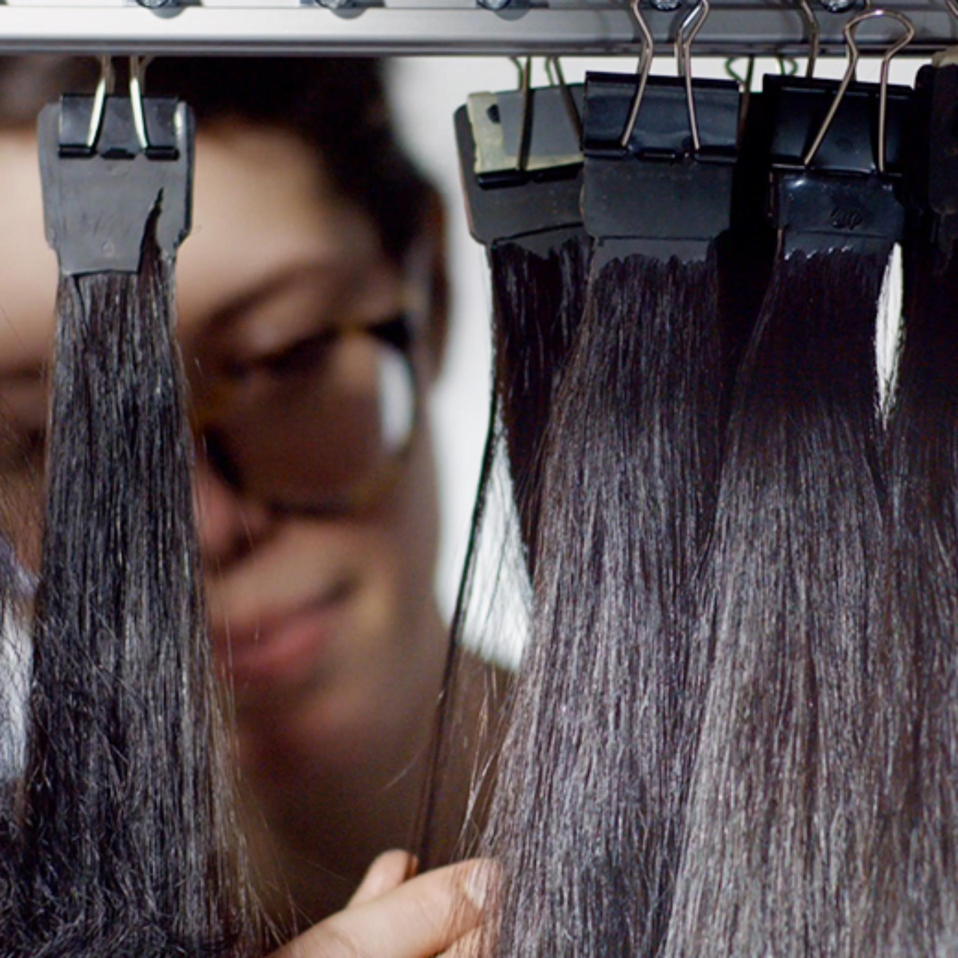 Real hair being tested in laboratory. The hair is clipped to a rail.