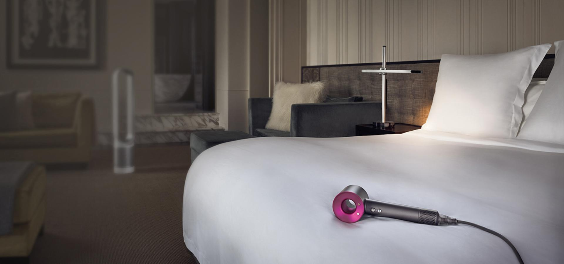 Dyson Supersonic™ hair dryer on bed